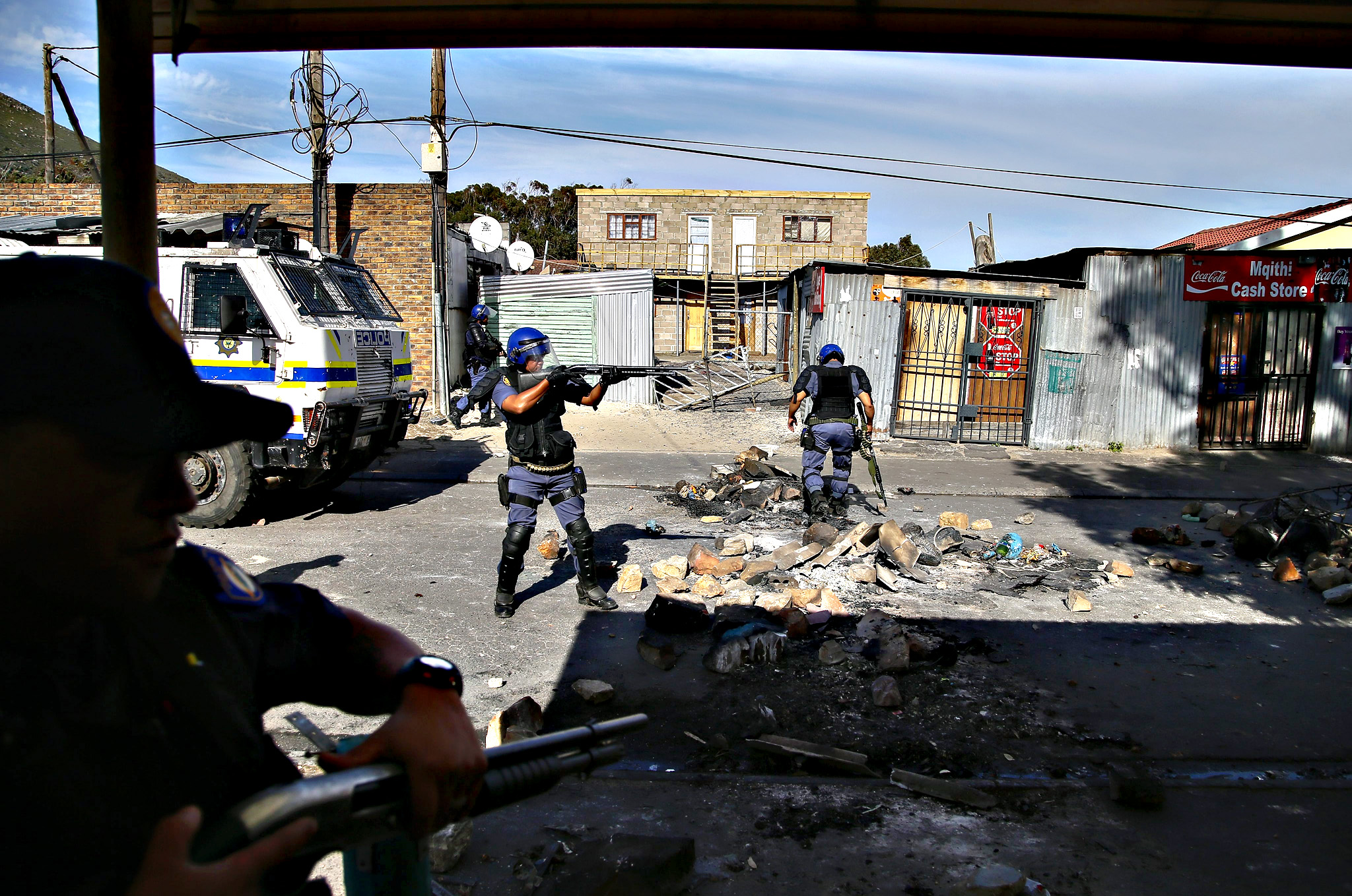 South African police fire rubber bullets to disperse residents of Masiphumelele during a protest against the police in Masiphumelele, Cape Town, South Africa  23 October 2015. Community members are angered at the arrest of some residents suspected to be vigilantes following the killing of suspected criminals by vigilantes. This follows weeks of protests over the lack of policing in the impoverished area and the alleged targetting of vigilante members by the police
