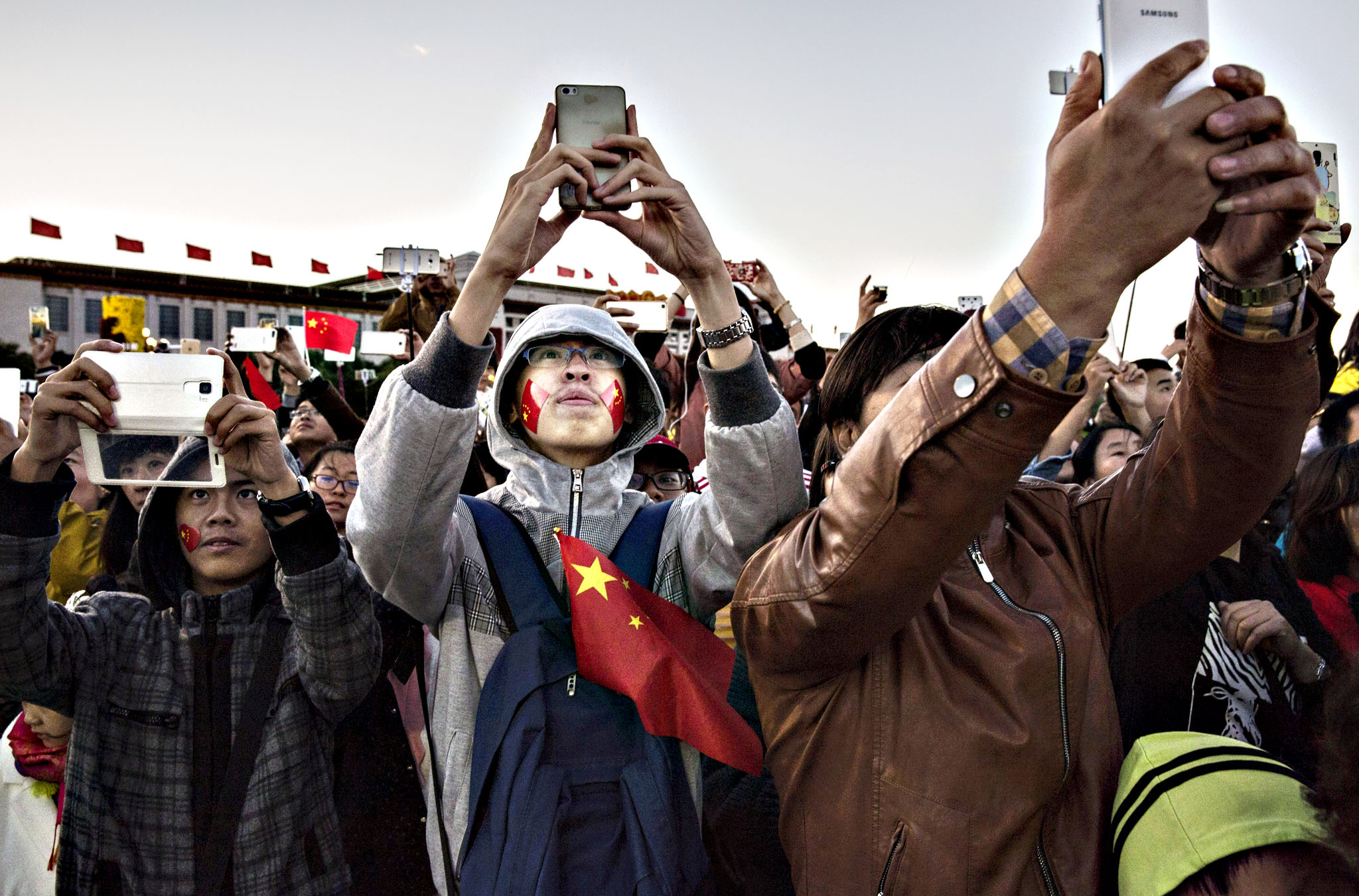 """People take pictures as they gather during the official flag raising ceremony at Tiananmen Square to mark the 66th National Day on October 1, 2015 in Beijing, China. China begins the """"Golden Week"""" holiday Thursday, as much of the country shuts down and financial markets close until October 8th"""