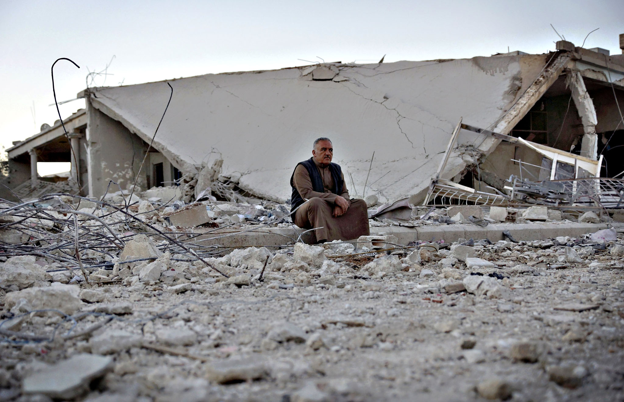 A man rests in a damaged site from what activists said was barrel bombs dropped by forces loyal to Syria's president Al-Assad in the southern town of Bosra al-Sham, Deraa province, Syria...A man rests in a damaged site from what activists said was barrel bombs dropped by forces loyal to Syria's president Bashar Al-Assad in the historic Syrian southern town of Bosra al-Sham, Deraa