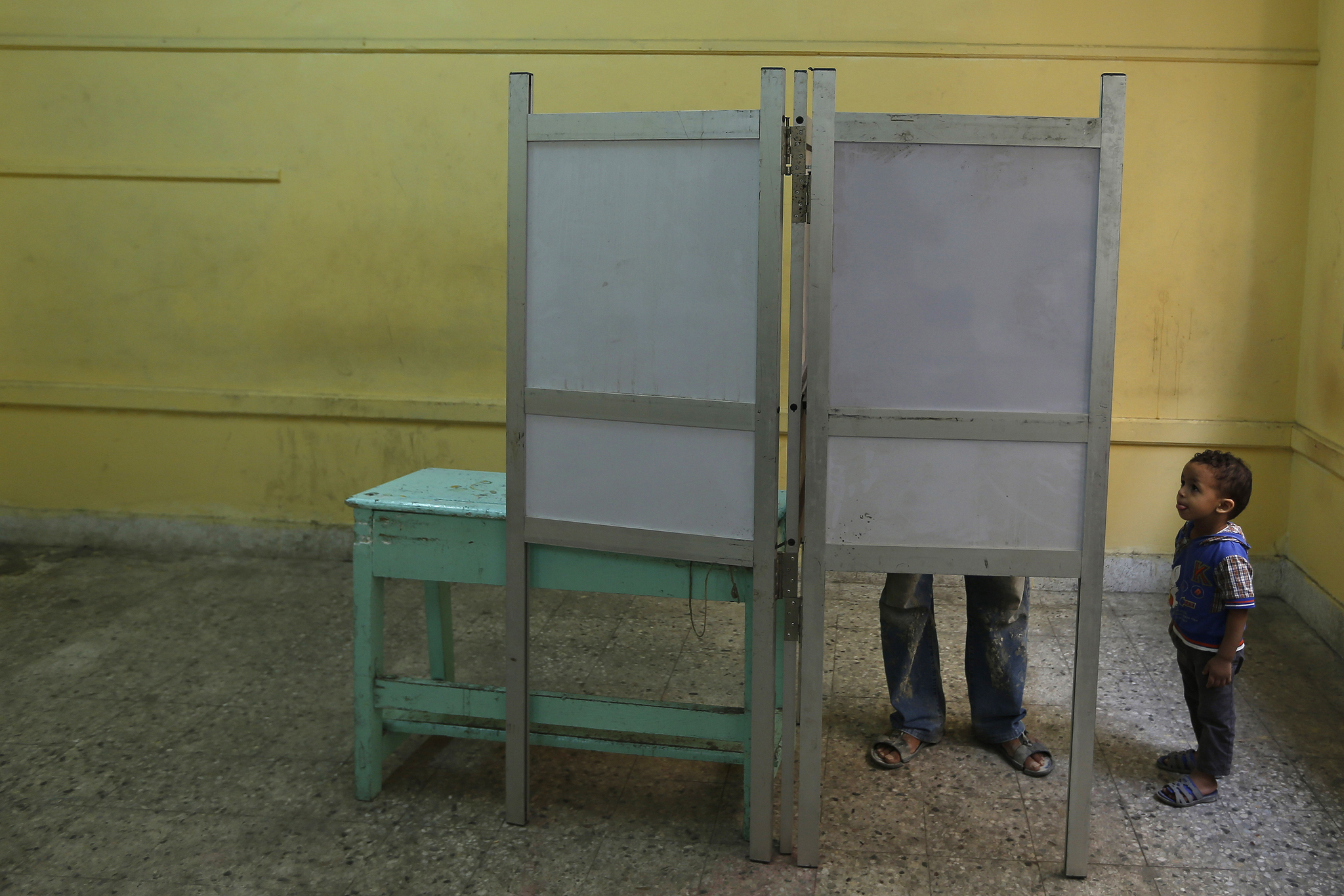 An Egyptian boy watches his father mark his ballot during the final day of the first round of the Egyptian parliamentary elections, at a polling station in Alexandria, Egypt, Sunday, Monday, Oct. 19, 2015. Egyptian authorities have given government workers a half-day off Monday in an attempt to bolster low turnout in the country's parliamentary election. The government has not released turnout figures for voting on Sunday. (AP Photo/Hassan Ammar)