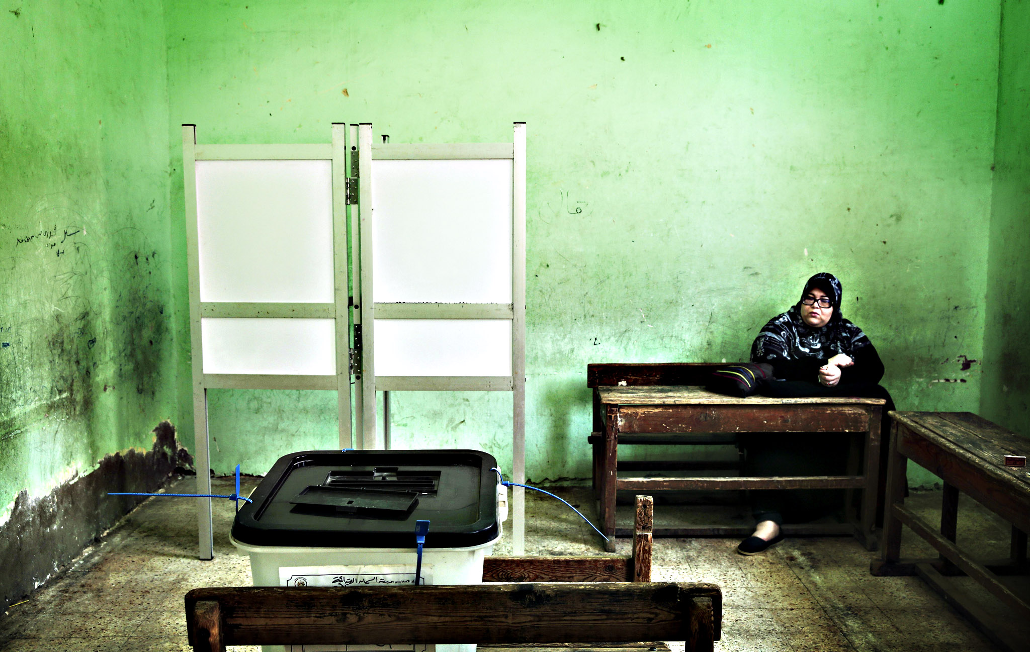 An election worker sits inside a polling station during the runoff of the first round of the parliamentary election, in Al-Haram in Giza, a neighboring city of Cairo, Egypt, Tuesday, Oct. 27, 2015.