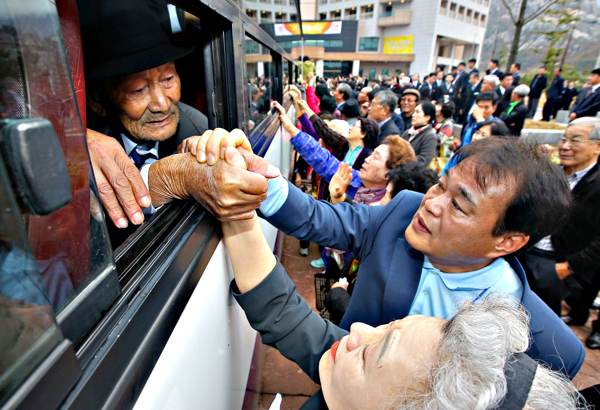 North Koreans grip hands of their South Korean relatives as they bid farewell after a separated family reunion meeting at the Mount Kumgang resort on the North's southeastern coast on October 22, 2015.  North and South Korean families divided by war for more than 60 years said a final, traumatic farewell on Thursday after a reunion event that, for most, marked the last time they will ever see each other