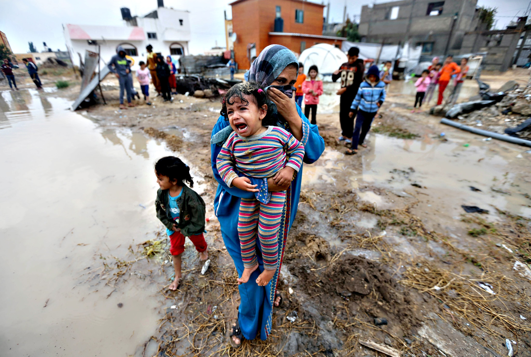 A Palestinian woman carries her crying daughter after rainwater flooded their house that witnesses said was damaged by Israeli shelling during the 50-day war in the summer of 2014,  in Khan Younis in the southern Gaza Strip October 7, 2015.