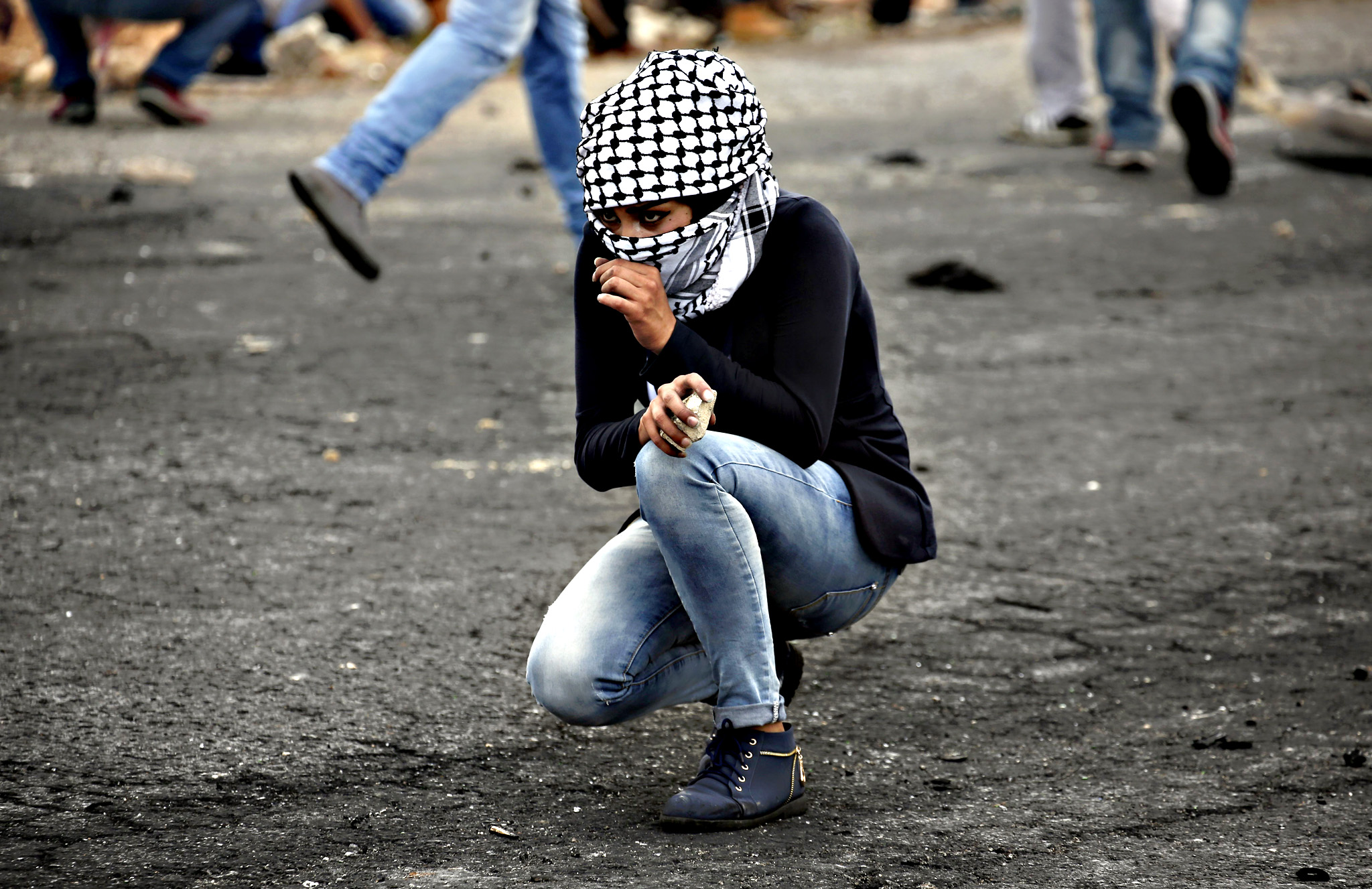 A Palestinian young woman from the Birzeit University looks on during clashes with Israeli security forces in Beit El, on the outskirts of the West Bank city of Ramallah, on October 7, 2015. New violence rocked Israel and the Israeli-occupied West Bank, including a stabbing in annexed east Jerusalem, even as Israel and Palestinian president Mahmud Abbas took steps to ease tensions