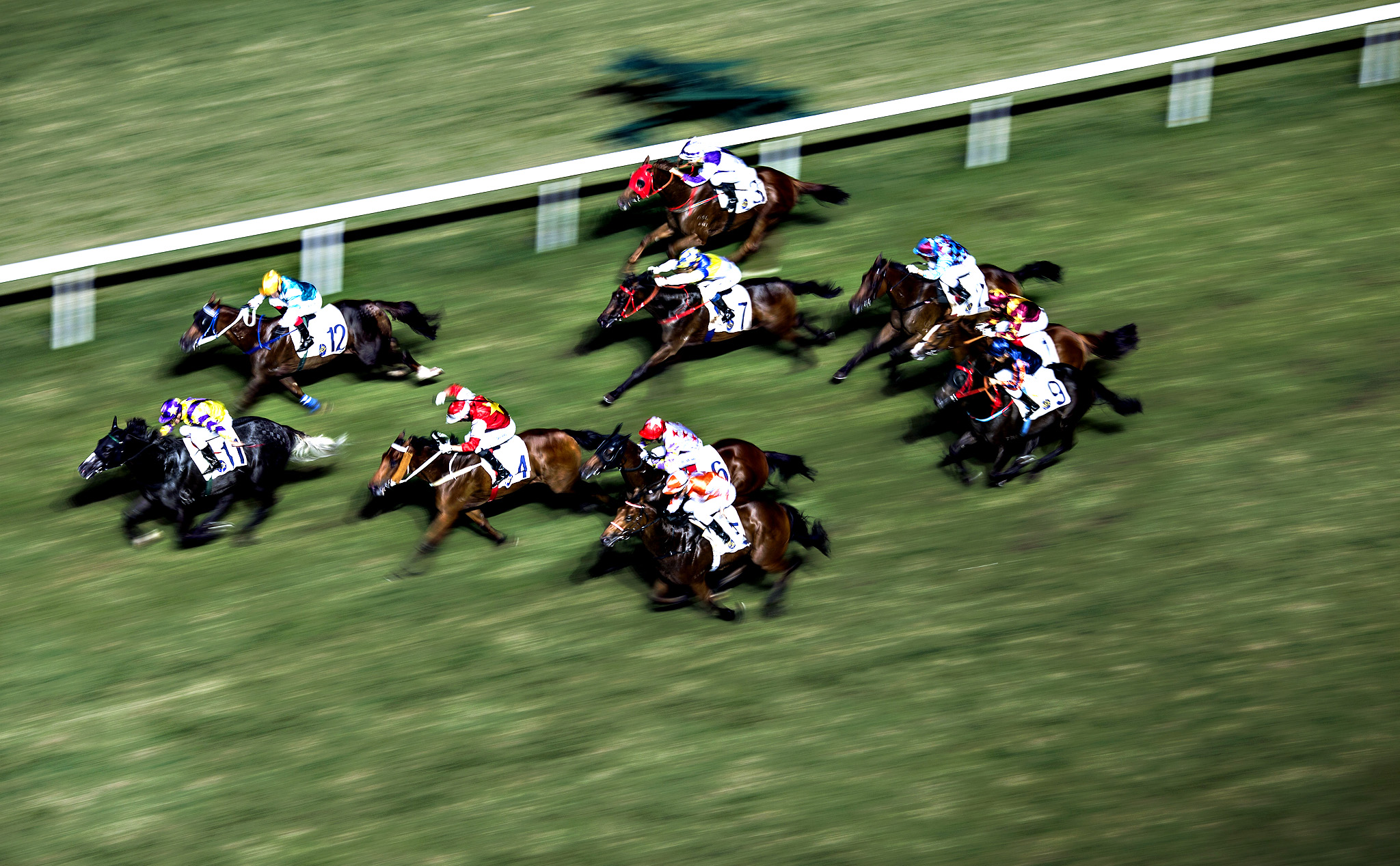 Horses gallop on the track during a race at the Hong Kong Jockey Club's Happy Valley racecourse in Hong Kong, China. The Hong Kong Jockey Club is the city's sole provider of horse racing, football betting and lotteries