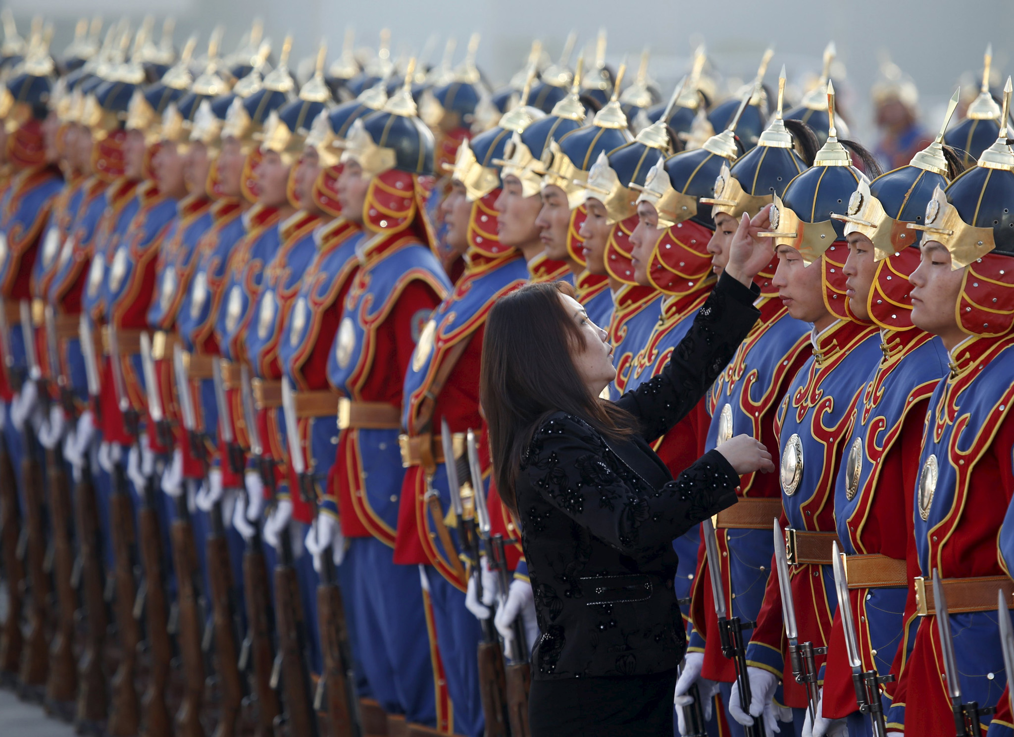A woman adjusts the hat of a member of the honour guards