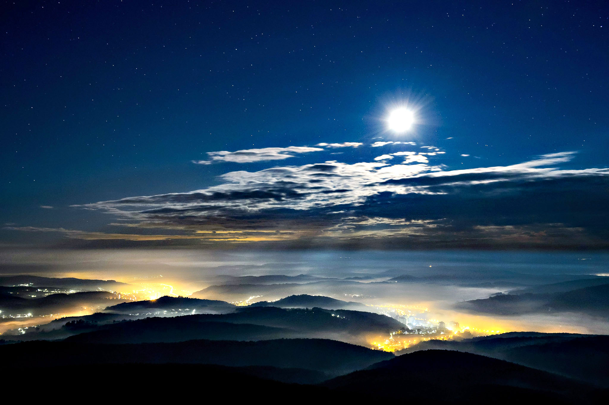 The Moon shining above a mountainous landscape under a cloudy sky near Salgotarjan, some 100km northeast of Budapest, Hungary