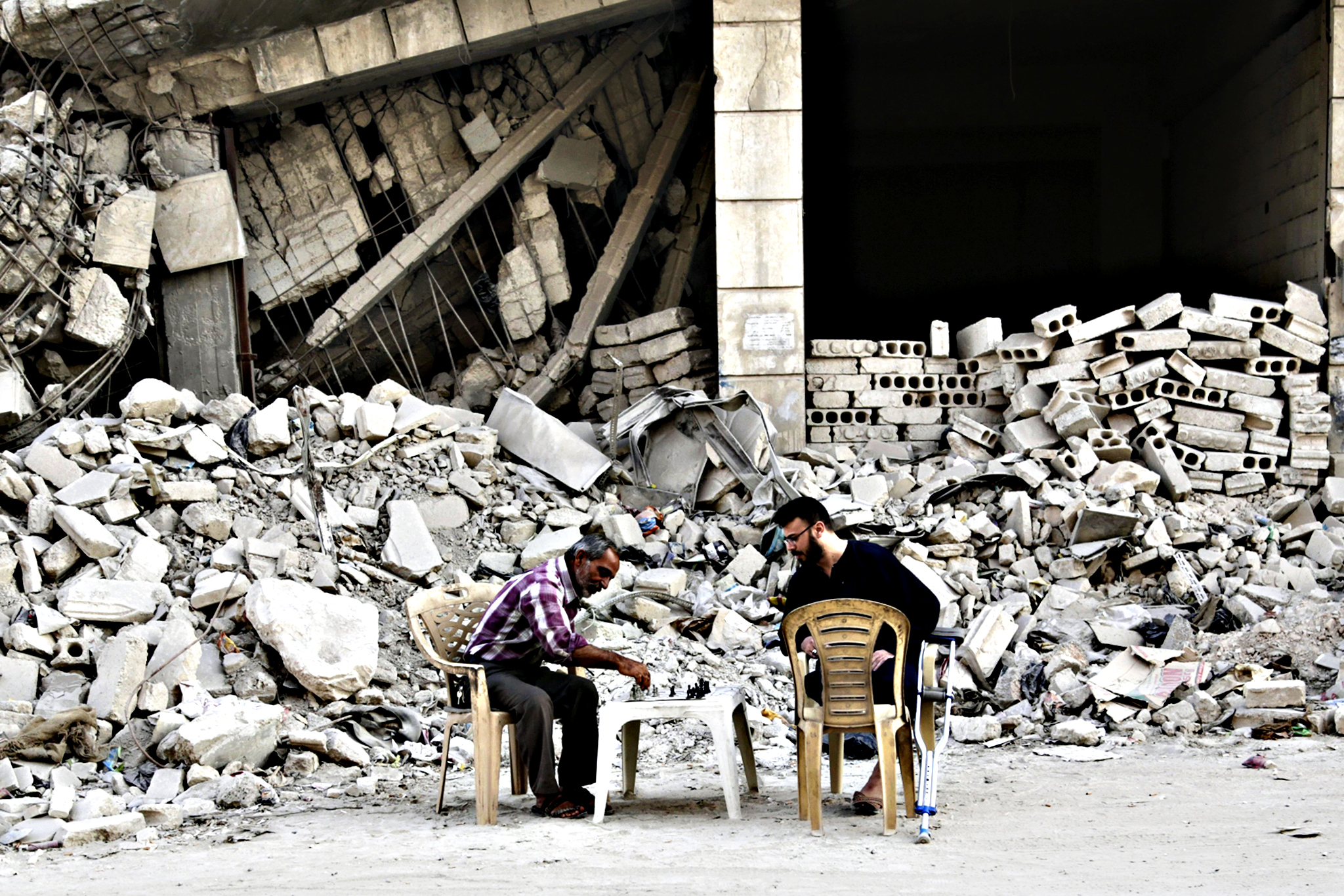 Men play chess in front of a damaged building in the rebel-controlled area of Maaret al-Naaman town in Idlib province, Syria...Men play chess in front of a damaged building in the rebel-controlled area of Maaret al-Naaman town in Idlib province, Syria October 19, 2015.