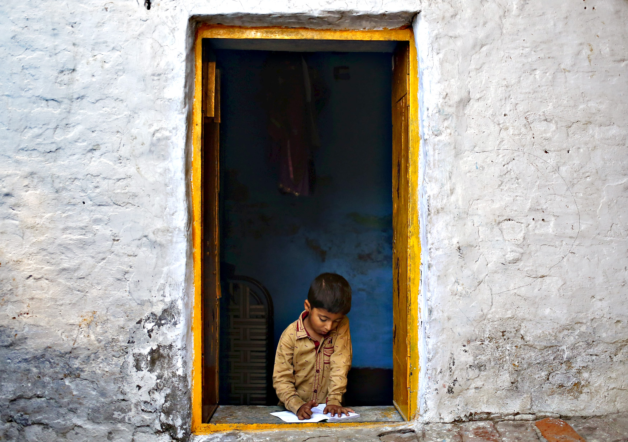 A boy studies at a window of his house at Dadri in Uttar Pradesh, India, October 2, 2015.