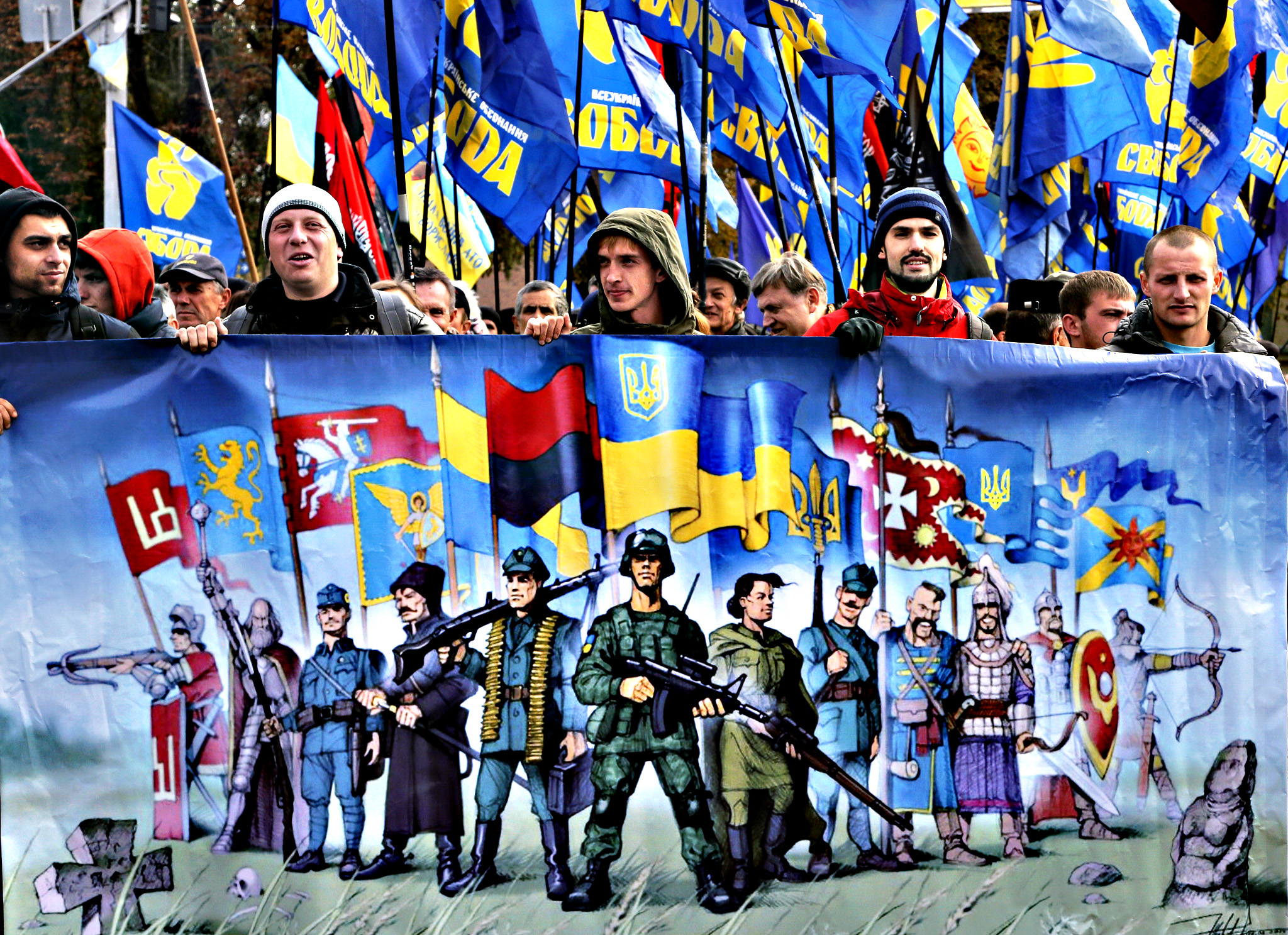 Activists of the of nationalist Svoboda (Freedom) party hold a poster and their flags during a  rally in Kiev, Ukraine, Wednesday Oct. 14, 2015. Ukraine is marking the 'Defender of the Fatherland Day'.