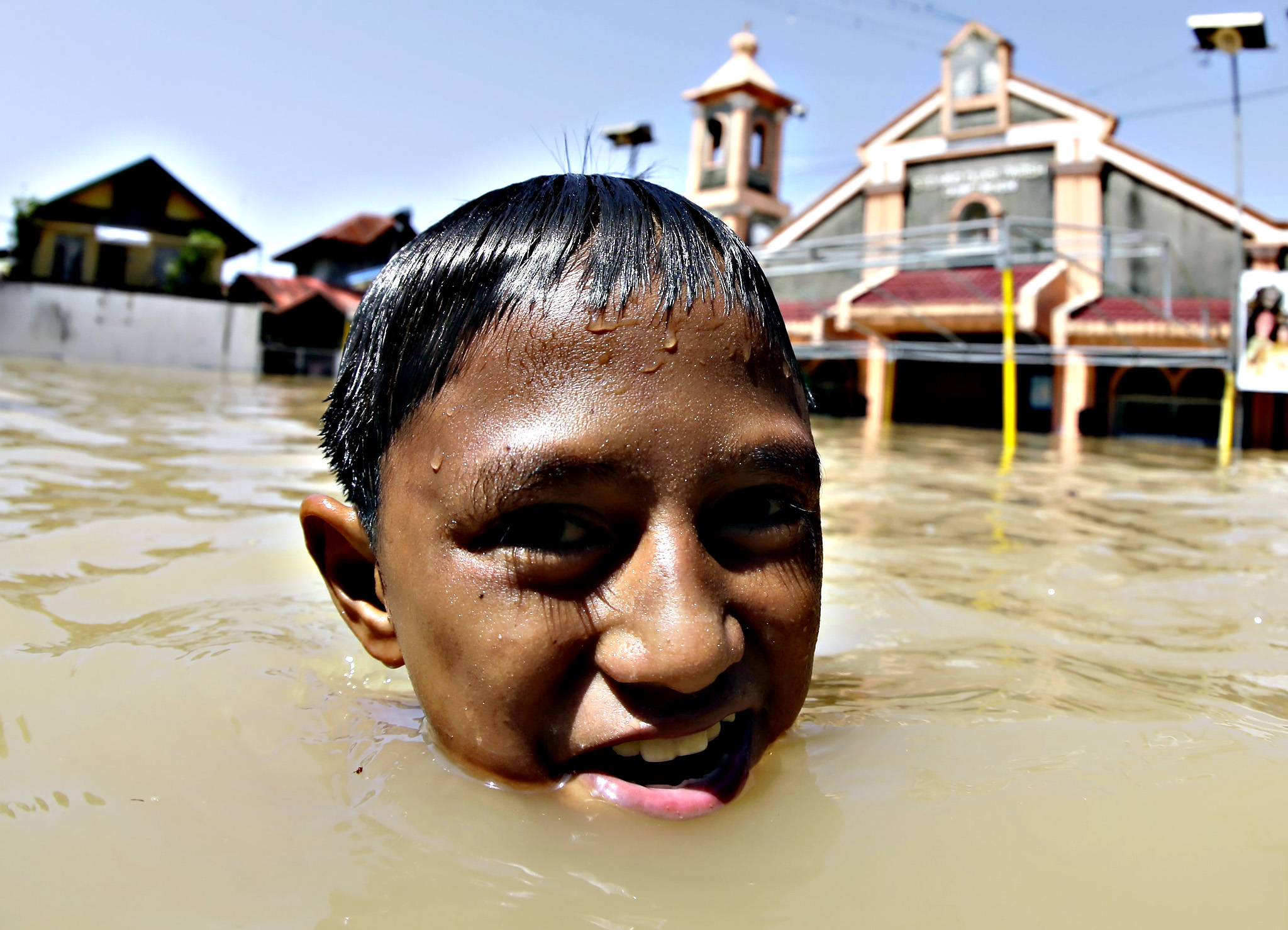 A Filipino boy wades next to a church at the flood-hit town of Calumpit, Bulacan province, northern Manila, Philippines, 21 October 2015. The death toll in a powerful storm that battered the northern Philippines has risen to 35, with nearly half a million people displaced, disaster relief officials said. Most of the fatalities either drowned in floods that reached up to the roofs in some areas, were buried in landslides, or hit by toppled trees or collapsed walls caused by typhoon Koppu. Koppu, which flooded rice-growing provinces, caused damage to agriculture and infrastructure worth at least 6.56 billion pesos (142.60 million dollars), the national disaster relief agency said
