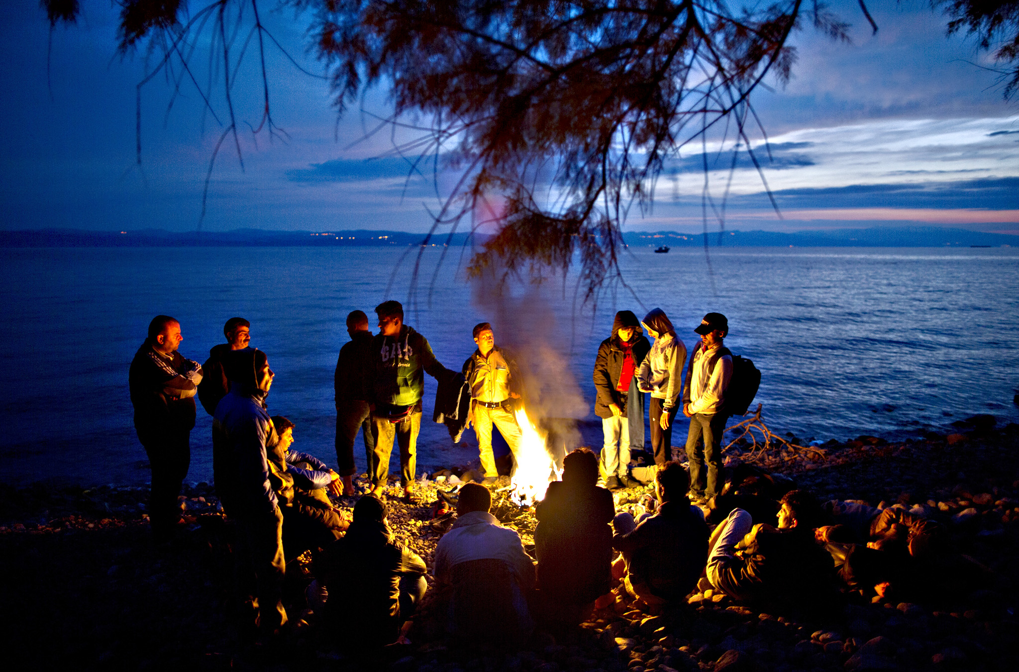 Syrian and Afghan refugees warm themselves and dry their clothes around a fire after arriving on a dinghy from the Turkish coast to the northeastern Greek island of Lesbos, early Wednesday, Oct. 7, 2015.