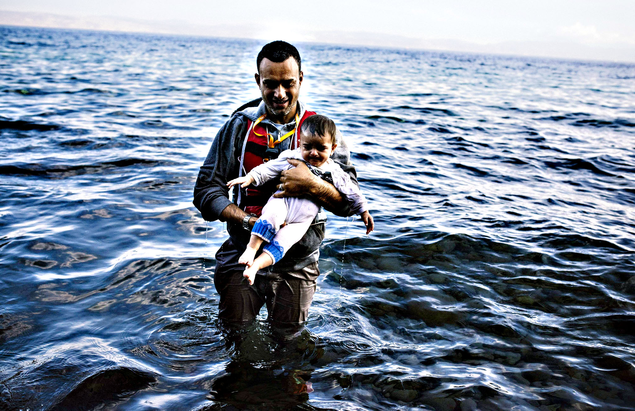 A man carries his child shortly after he arrived, with other refugees and migrants, on the Greek island of Lesbos, after crossing the Aegean sea from Turkey, on October 12, 2015. Greece was hit by a huge new surge in migrants as the United Nations on October 9 approved a European seize-and-destroy military operation against people smugglers in the Mediterranean.