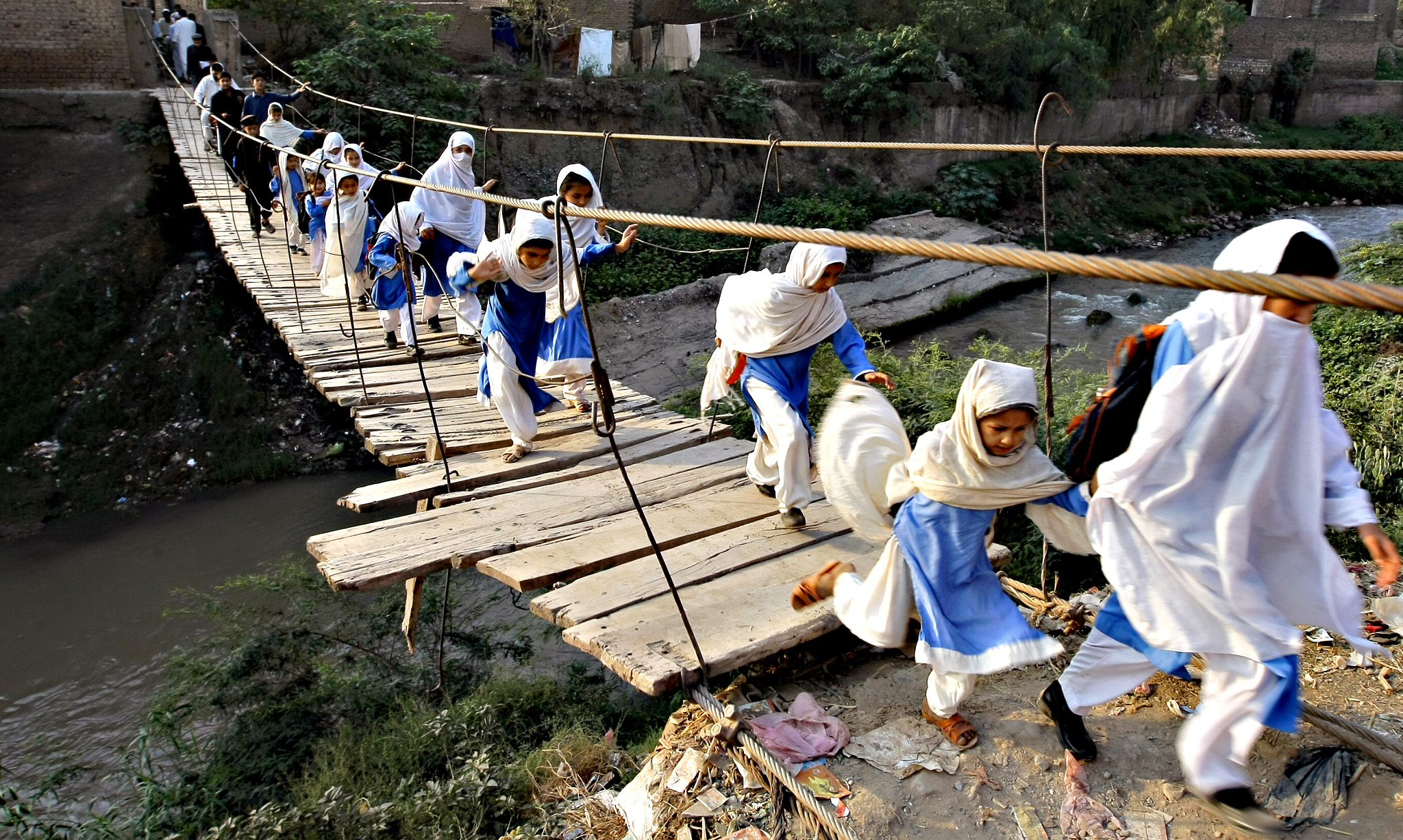 Pakistani students cross a makeshift bridge in Peshawar, Pakistan, Tuesday, Oct. 6, 2015. The previous bridge was washed away in a flood.