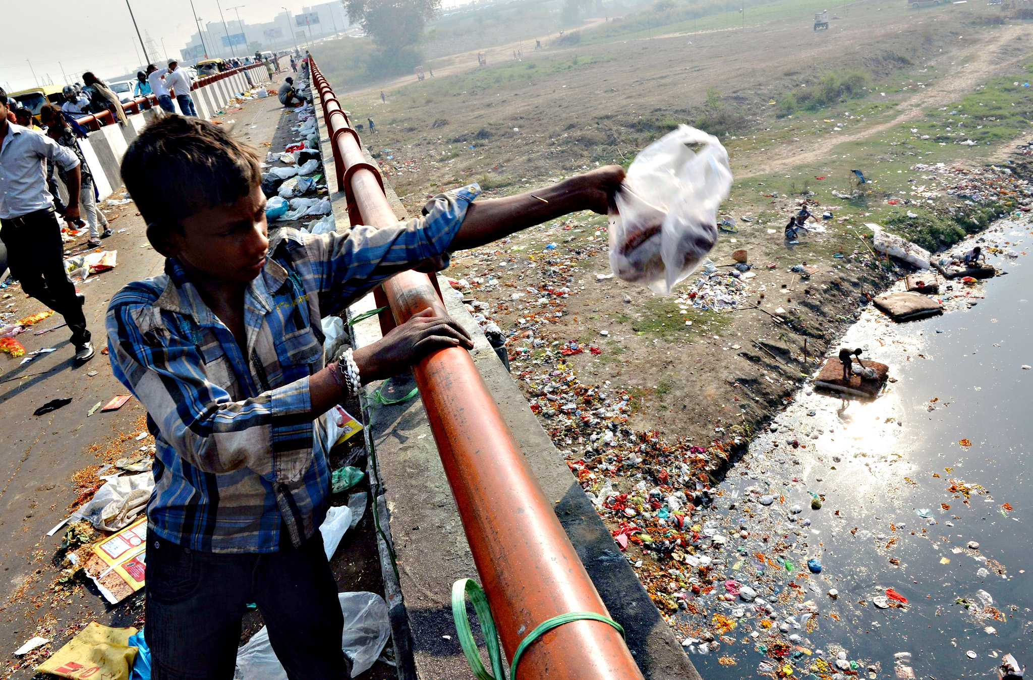 An Indian boy throws domestic garbage into the already polluted Yamuna river in New Delhi on October 23, 2015. Considered one of the holiest rivers in India, the Yamuna River has been dying a slow death from pollution for decades despite the investment of millions of dollars to preserve its ecosystem. According to the Central Pollution Control Board (CPCB) which monitors the water quality of the Yamuna in Delhi, seventy percent of the pollution in the river is from untreated sewage while the remaining thirty percent is from industrial sources, agricultural run-off and domestic garbage