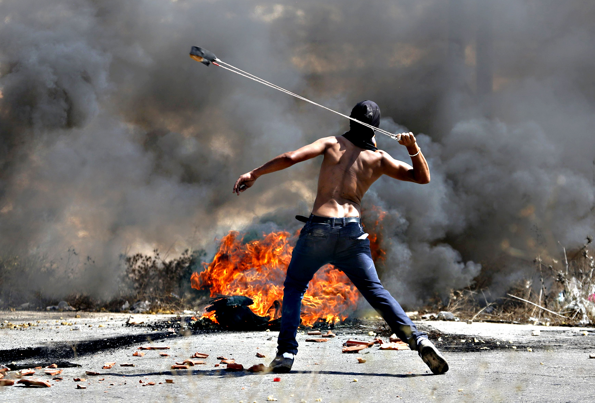 Palestinian protester uses a sling to hurl stones towards Israeli troops during clashes near the Jewish settlement of Bet El, near the occupied West Bank city of Ramallah...A Palestinian protester uses a sling to hurl stones towards Israeli troops during clashes near the Jewish settlement of Bet El, near the occupied West Bank city of Ramallah October 5, 2015. Violence intensified in Jerusalem and the West Bank on Sunday after Israelis were targeted in two stabbing attacks and a Palestinian was killed in a clash with Israeli troops, officials said