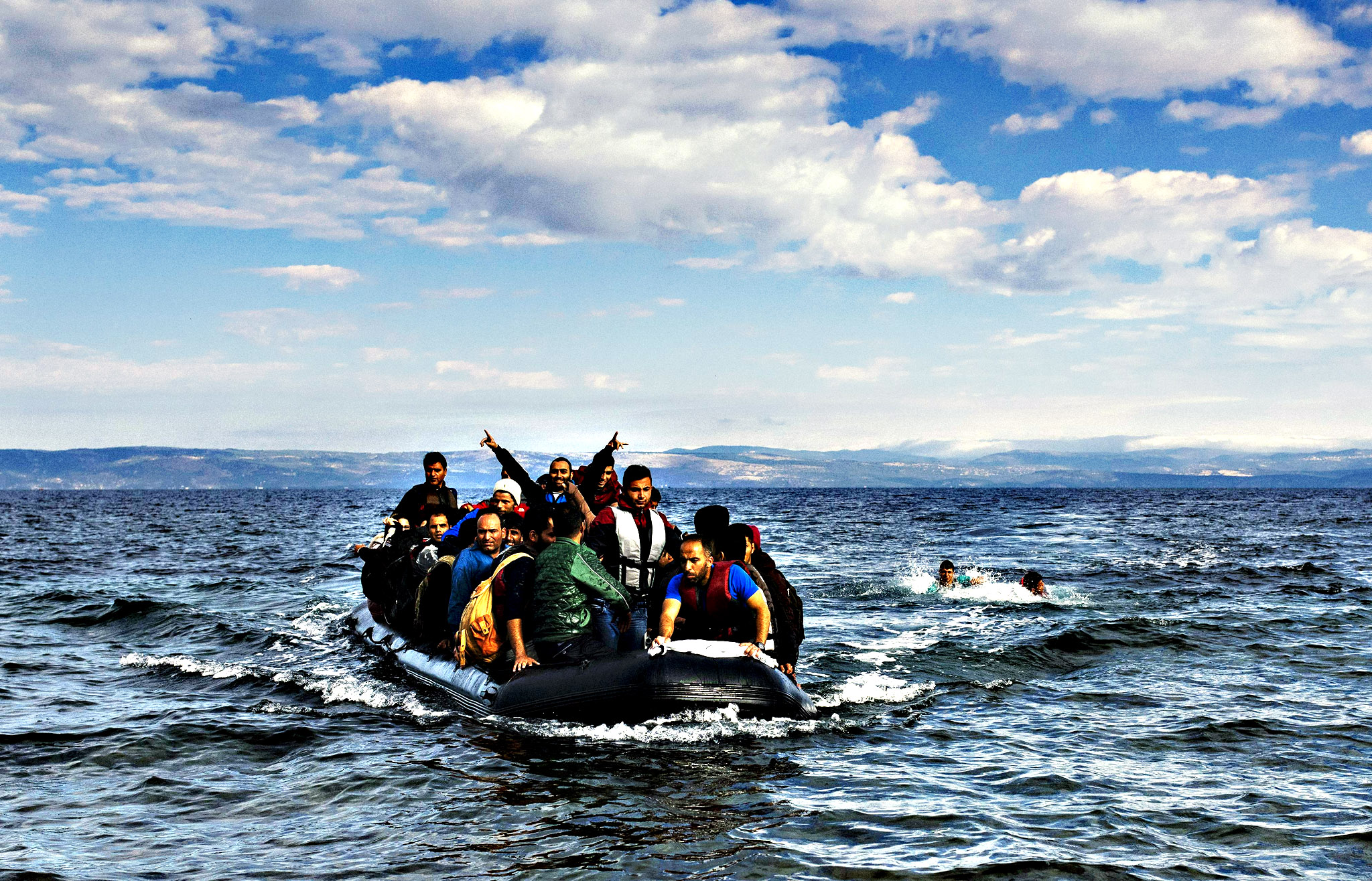 Refugees and migrants arrive on a rubber boat on the Greek island of Lesbos after crossing the Aegean sea from Turkey on October 13, 2015. Greece pledged On October 10, 2015 during talks with its EU partners to open its first so-called hotspot reception centre on the island of Lesbos within 10 days under EU efforts to better deal with the massive influx of migrants.
