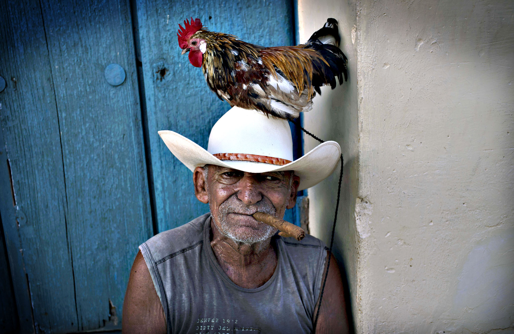 Jose poses with his rooster named Luis to be photographed for tourists in Trinidad, Cuba.
