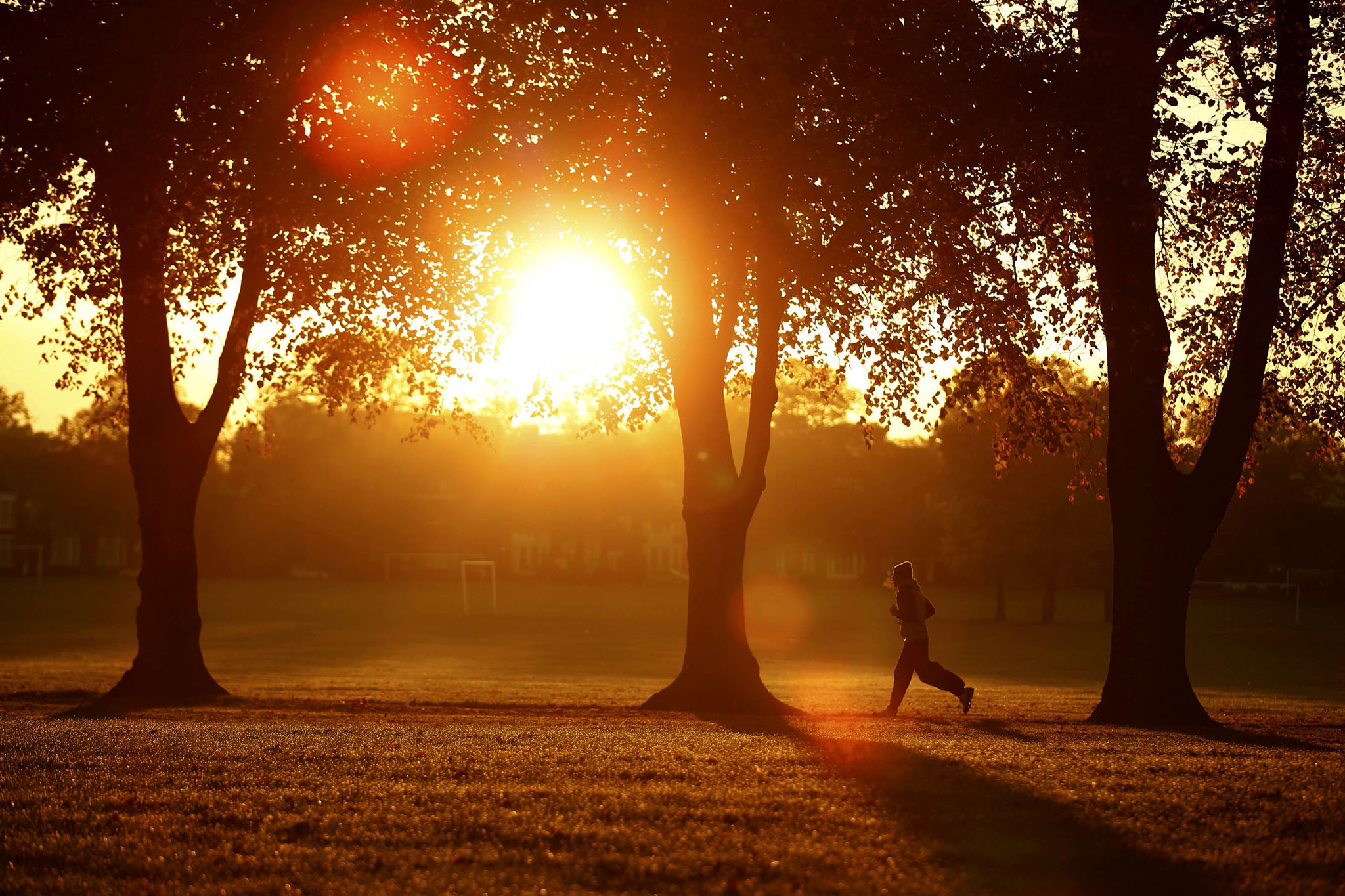 A woman runs through Victoria Park at sunrise in Leicester