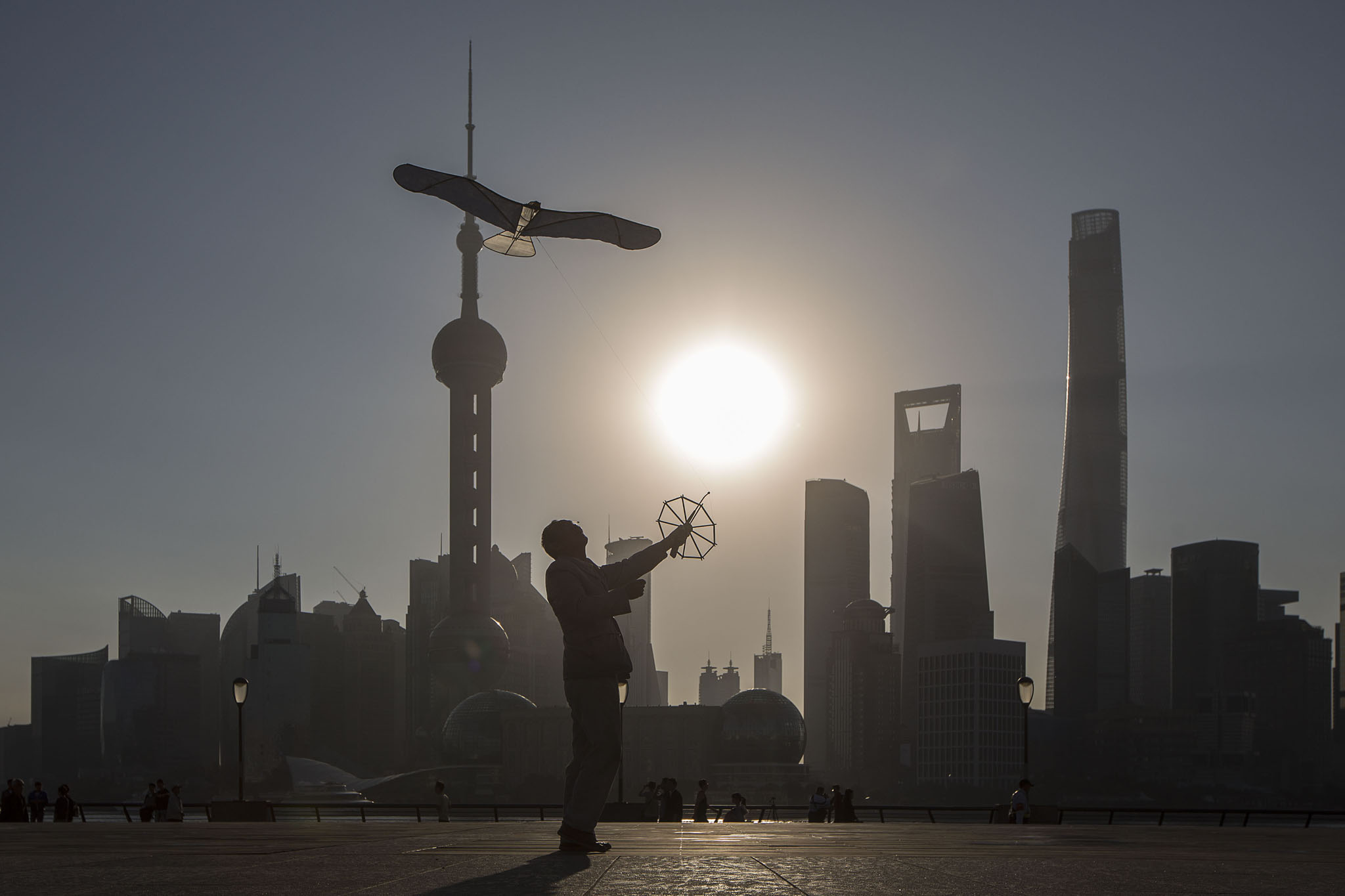 A man flies a kite on the Bund while buildings of Pudong's Lujiazui financial district stand across the Huangpu River as the sun rises in Shanghai, China