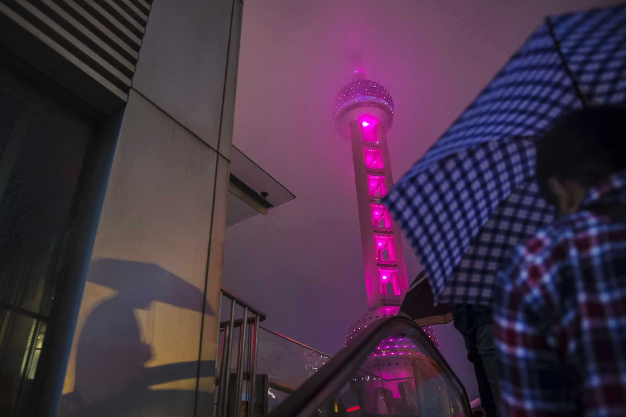 A pedestrian holding an umbrella rides up an escalator as the Oriental Pearl Tower stands illuminated at night