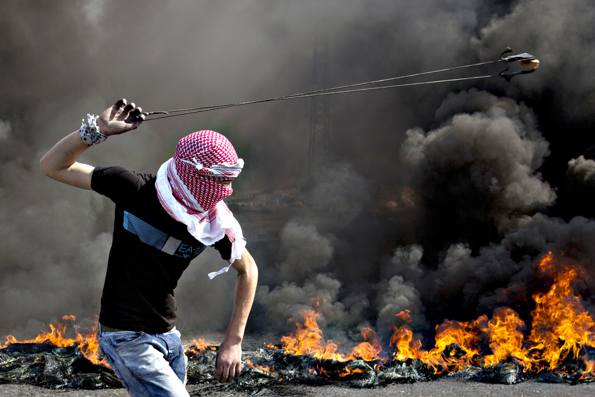 A Palestinian swings a sling during clashes with Israeli troops, near Ramallah, West Bank,  Tuesday, Oct. 20, 2015. U.N. Secretary-General Ban Ki-moon called for calm during a surprise visit to Jerusalem on Tuesday ahead of meetings with Israeli and Palestinian leaders, in a high-profile gambit to bring an end to a monthlong wave of violence