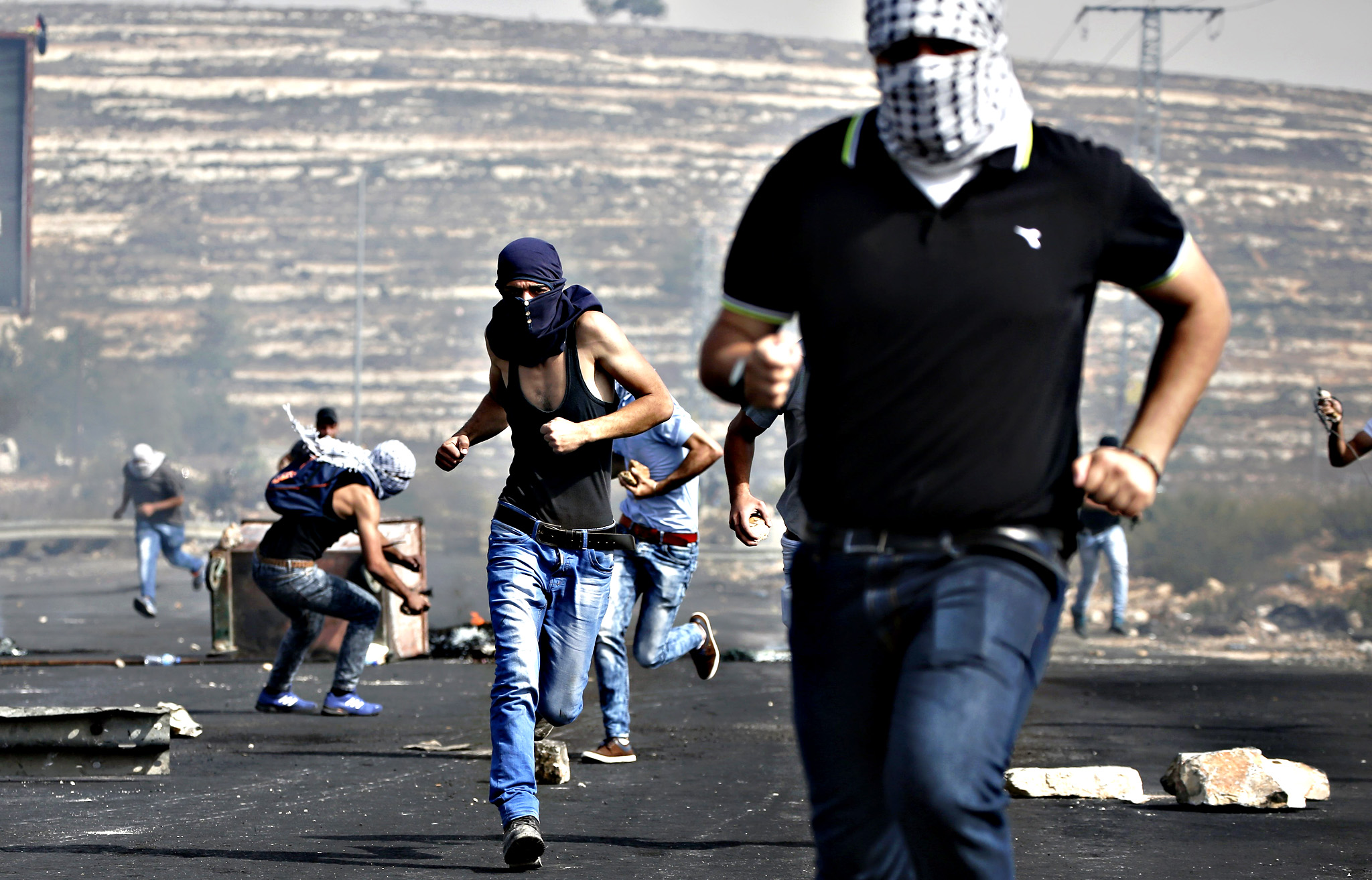 "Palestinian protestors take cover during clashes with Israeli security forces near the Jewish settlement of Beit El, just north of the West Bank city of Ramallah, on October 12, 2015. Palestinian foreign minister Riad al-Malki accused Israel of seeking to spark ""a third intifada"", as violence again flared in Jerusalem, the West Bank and the Gaza Strip."