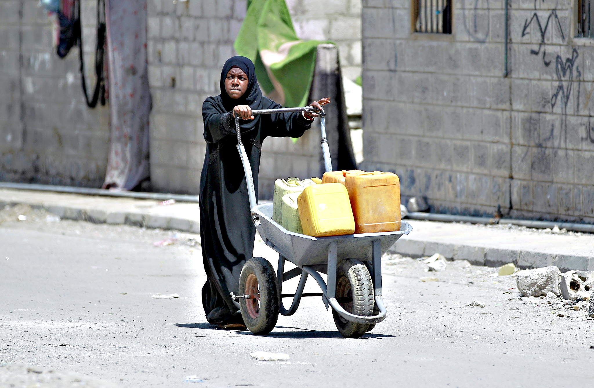 A Yemeni woman carries jerrycans to fill them with water from a public tap amid an acute shortage of water supply to houses in the Yemeni capital, Sanaa on October 8, 2015.
