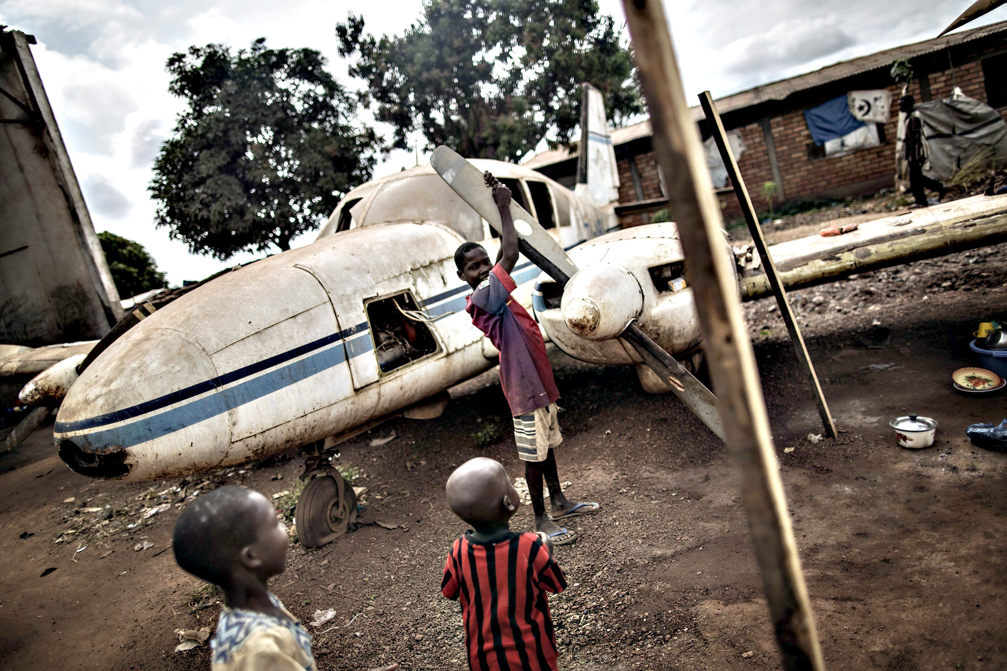"Children play with the wreckage of a light plane at the Mpoko Internally Displaced People (IDP) camp in Bangui on Thursday, ahead of a historical visit by the pope. Pope Francis held his first open-air mass in Africa on November 26 with huge crowds calling heavy rains ""God's blessing"" as they sung and danced in the Kenyan capital. The 78-year-old pontiff, the third pope to visit the continent, is also scheduled to visit Uganda and the troubled Central African Republic (CAR) on a six-day trip."