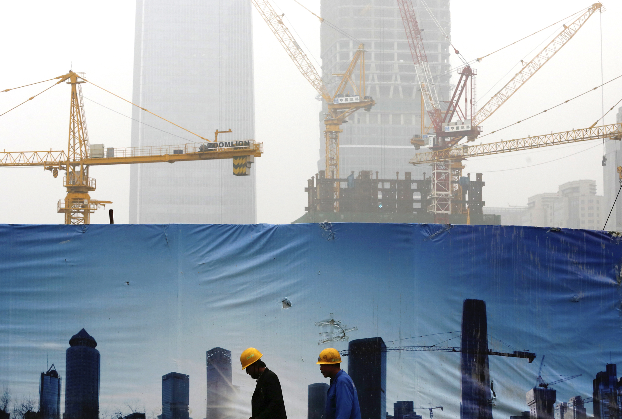 Workers walk past a billboard display showing a scene of Central Business District, as capital city skylines are shrouded with pollutant haze in Beijing, China, Monday, Nov. 9, 2015. Heading into this month's Paris meeting, the world's biggest source of climate-changing gases has yet to accept binding limits. But it has invested in solar, wind and hydro power to clean up its smog-choked cities and curb surging demand for imported oil and gas. That contributed last year to a surprise fall in coal consumption. (AP Photo/Andy Wong)