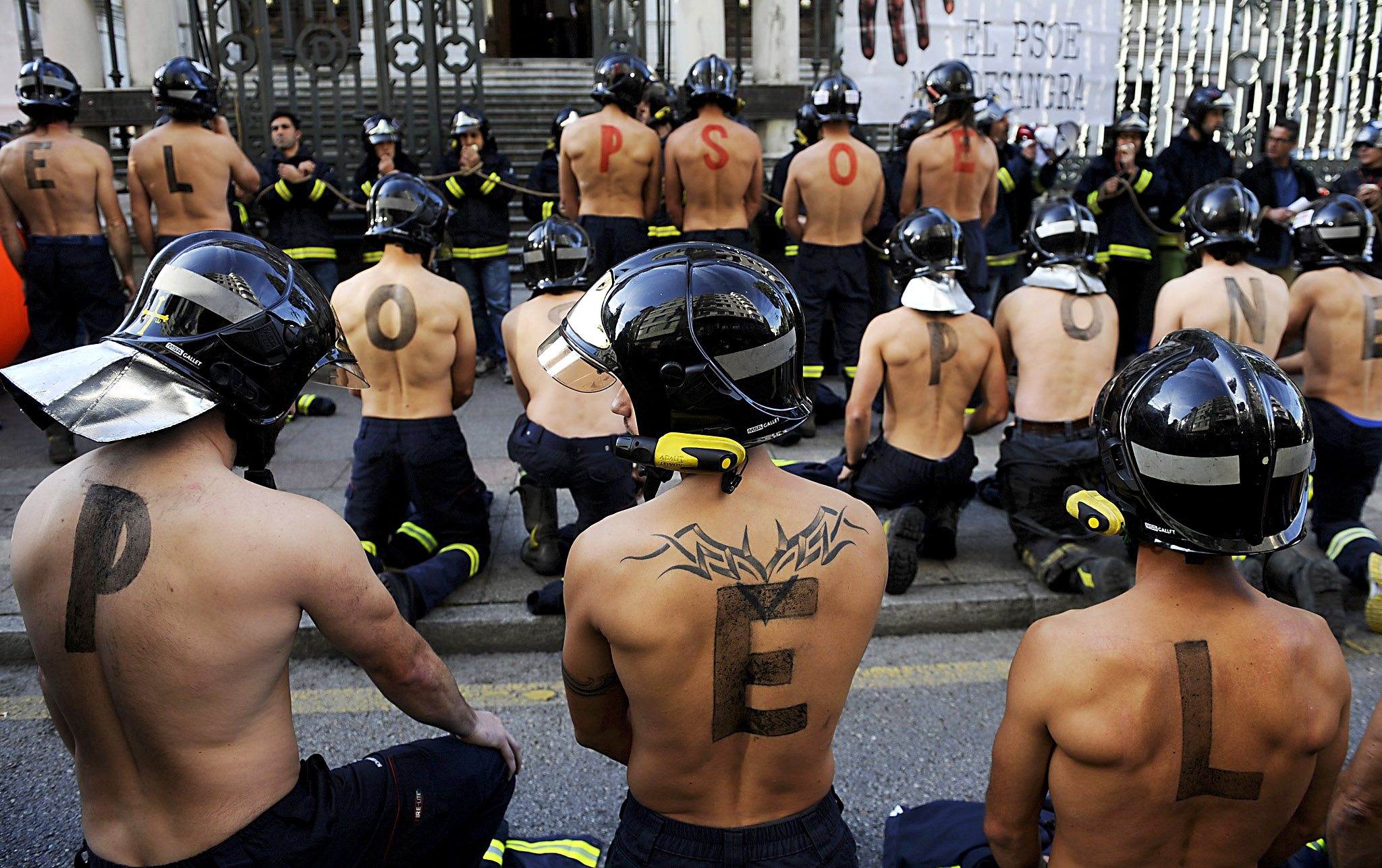 "Firefighters take part in a protest in front of the regional parliament of Asturias demanding better salaries and greater standards of public safety in Oviedo, northern Spain...Firefighters take part in a protest in front of the regional parliament of Asturias demanding better salaries and greater standards of public safety in Oviedo, northern Spain, November 19, 2015. The letters painted on the firefighters' backs form the words, ""The PSOE (Socialist Party of Spain) puts you in danger"""