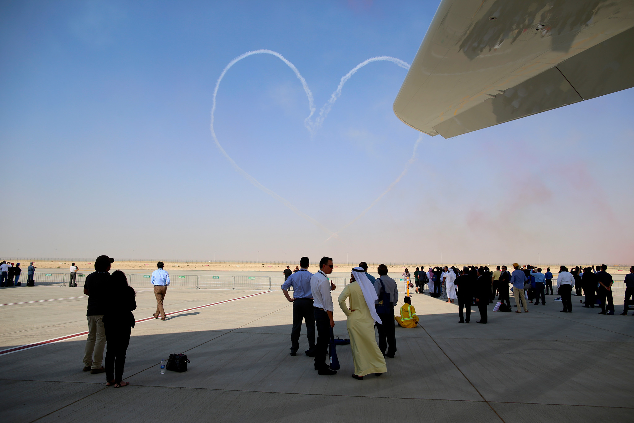 Day Two Of Dubai Air Show 2015...Visitors watch the Al Fursan aerobatic team perform an aerial display on the second day of the 14th Dubai Air Show at Dubai World Central (DWC) in Dubai, United Arab Emirates, on Monday, Nov. 9, 2015. The Dubai Air Show is the biggest aerospace event in the Middle East, Asia and Africa and runs Nov. 8 - 12. Photographer: Jasper Juinen/Bloomberg