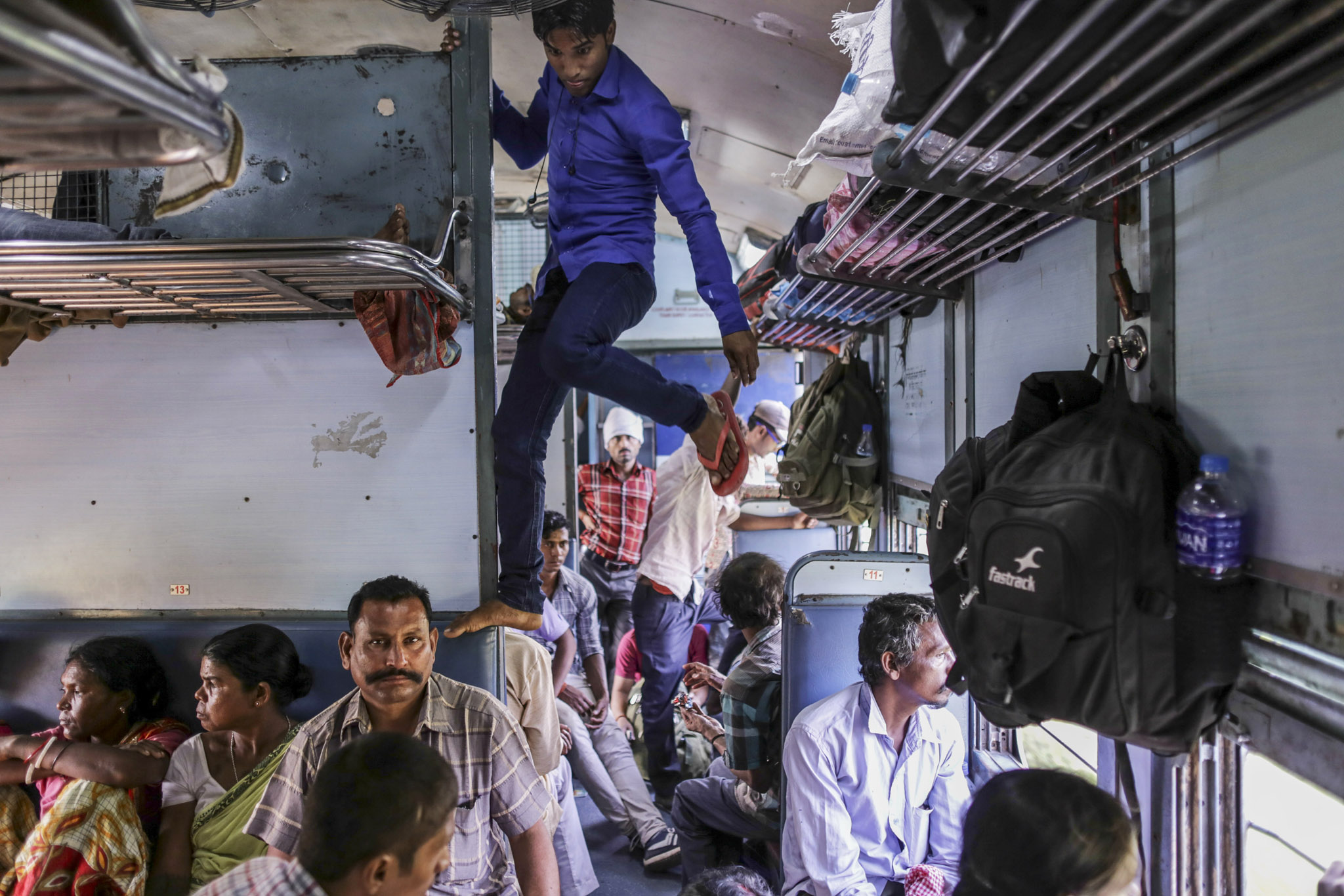 Dysfunction Junction: Railway Puts India on Slow Train to Future...A passenger climbs on a seat and luggage racks on the Kalka Mail train awhile traveling from Fatehpur station to Allahabad Junction station near Fatehpur, Uttar Pradesh, India, on Tuesday, Sept. 29, 2015. The 162-year-old system is Asia's oldest. It is the nation's economic artery, employer of more than 1.3 million people, and the government's most intractable problem. Unclogging its 65,000 kilometers of track is vital to any effort to develop the economy. Photographer: Dhiraj Singh/Bloomberg