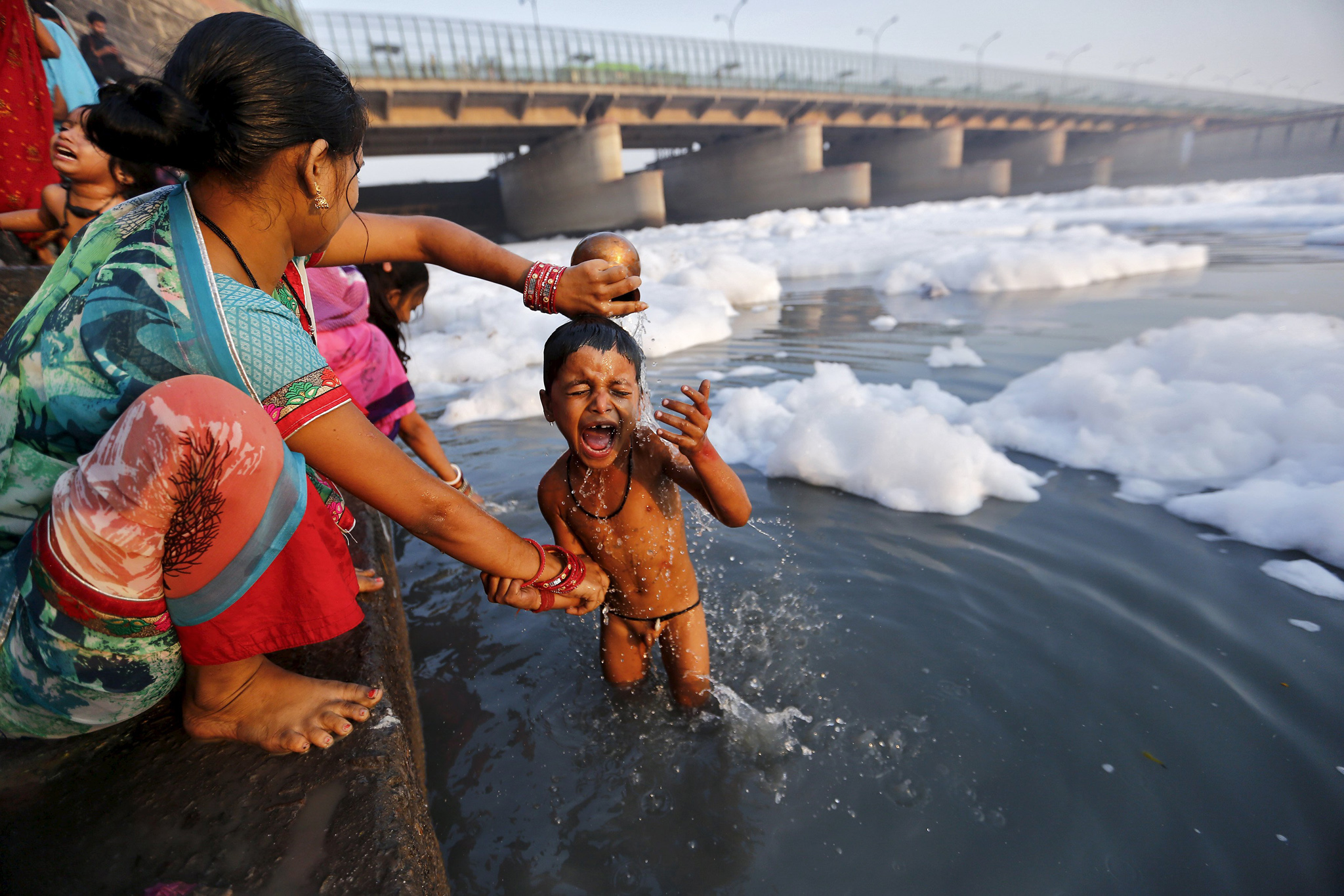 A woman bathes her child after worshipping the sun god Surya in the polluted waters of Yamuna river during the Hindu religious festival of Chatt Puja in New Delhi...A woman bathes her child after worshipping the sun god Surya in the polluted waters of Yamuna river during the Hindu religious festival of Chatt Puja in New Delhi, India, November 18, 2015. Hindu women fast for the whole day for the betterment of their families and the society during the festival. REUTERS/Anindito Mukherjee  TEMPLATE OUT
