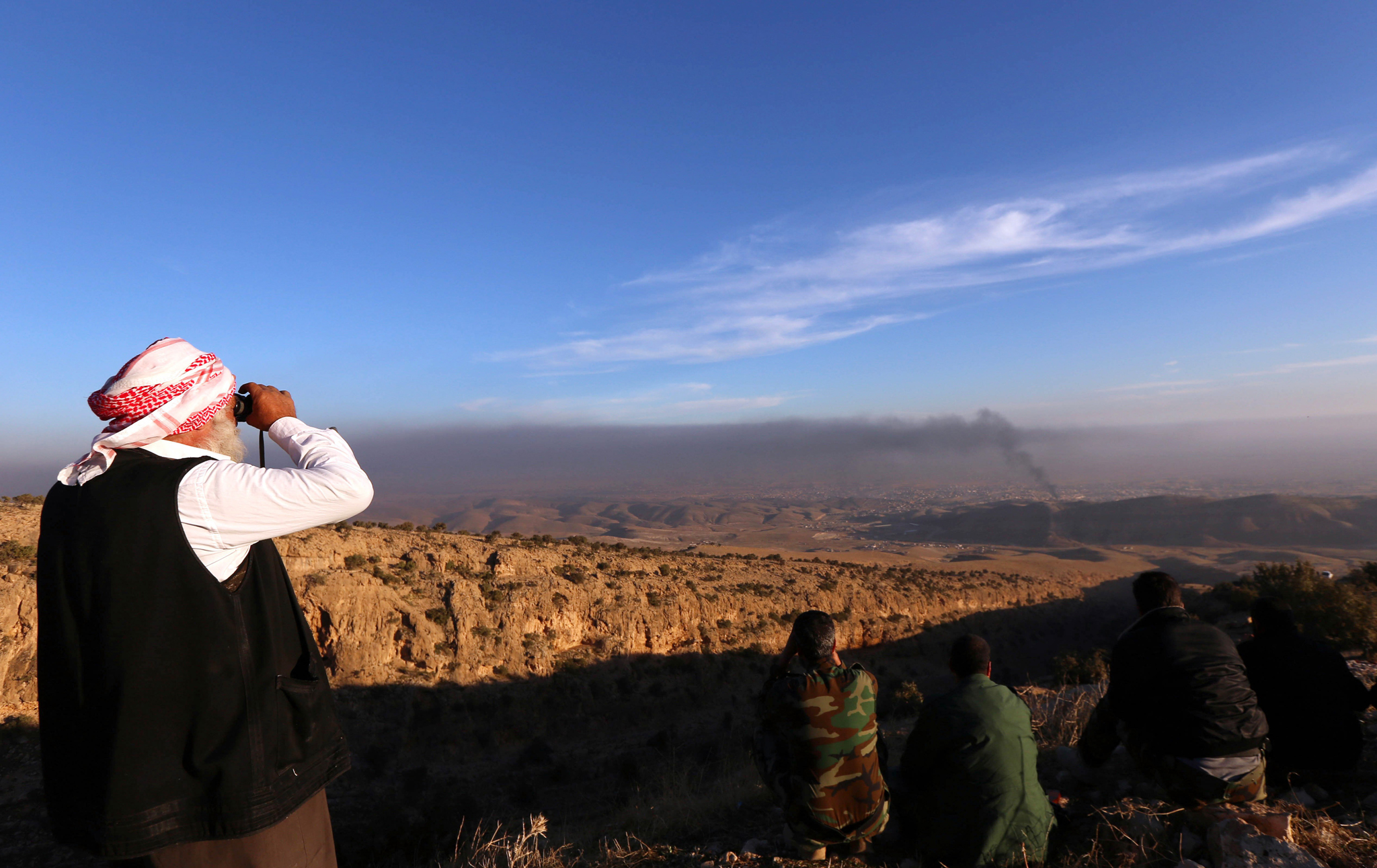 A displaced Iraqi man (L) from the Yazidi community, who fled violence between Islamic State (IS) group jihadists and Peshmerga fighters in the Iraqi town of Sinjar, in the northern Iraqi province of Mosul, looks on as smoke billows during an operation by Iraqi Kurdish forces backed by US-led strikes in the northern Iraqi town of Sinjar on November 12, 2015, to retake the town from the Islamic State group and cut a key supply line to Syria. AFP PHOTO / SAFIN HAMEDSAFIN HAMED/AFP/Getty Images