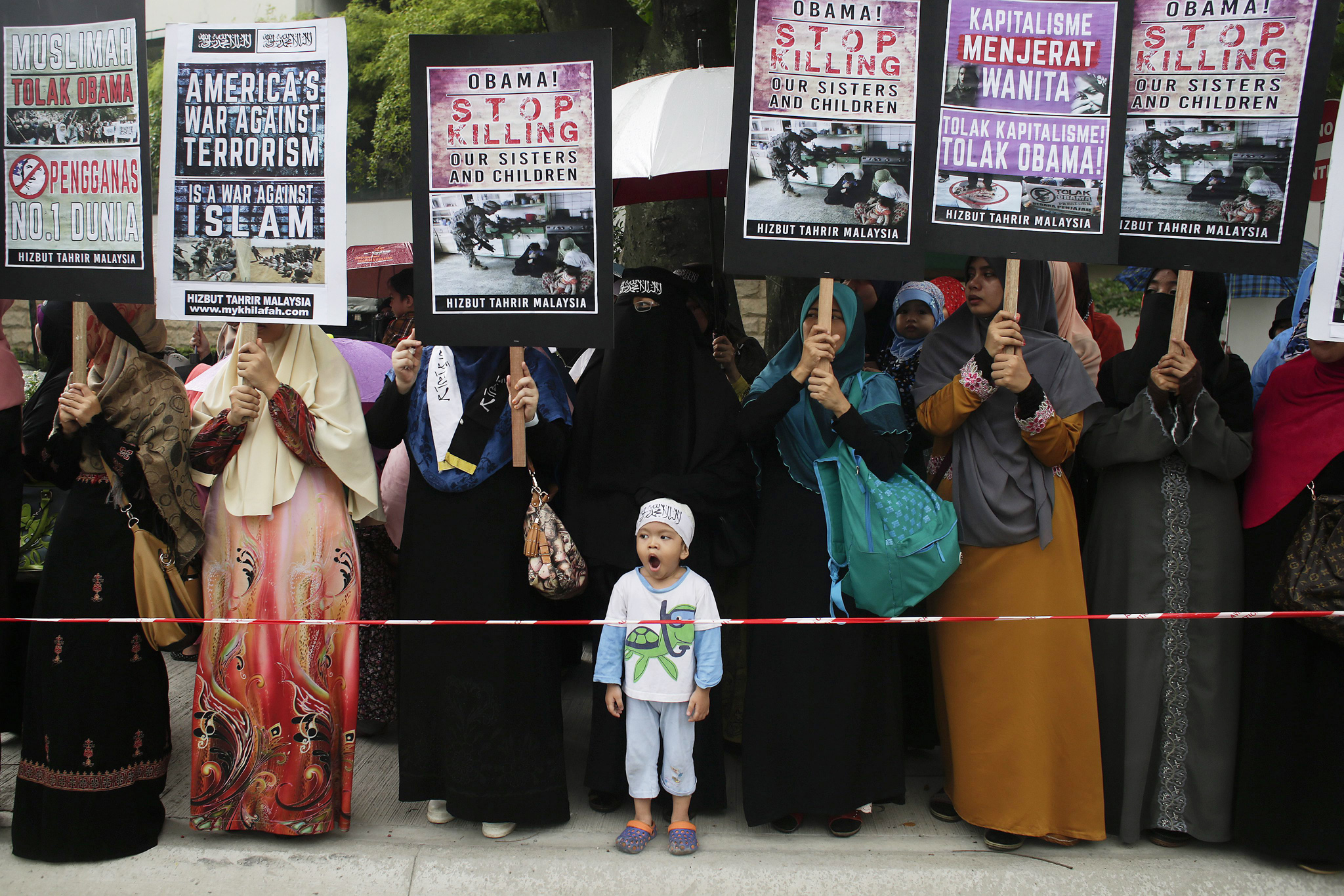 Malaysian Protest On US President Barrack Obama During ASEAN Summit...epa05022751 A child infront of protesters from Hizbut Tahrir Malaysia Islamic group holding placards during a protest in front of the US embassy in Kuala Lumpur, Malaysia, 13 November 2015. Hizbut Tahrir Malaysia labelled Obama as an 'enemy' of Islam, citing the deaths of Muslims in Iraq, Afghanistan, as well as in the ongoing Syrian conflict, which they blame on the US Presidentís administration  EPA/FAZRY ISMAIL