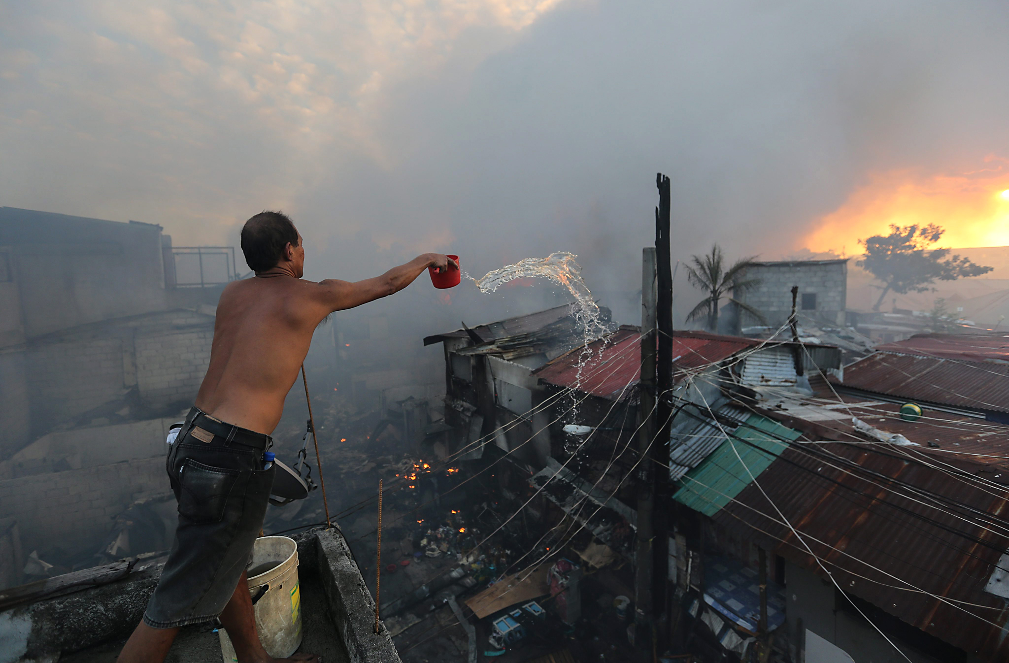 Fire razes homes in Mandaluyong, Manila...epa05040806 Filipino, Fil Binay (L) battles to contain a fire in Mandaluyong City, east of Manila, Philippines, 25 November 2015. The cause of the fire which reached the general alarm is still unknown.  EPA/MARK R. CRISTINO