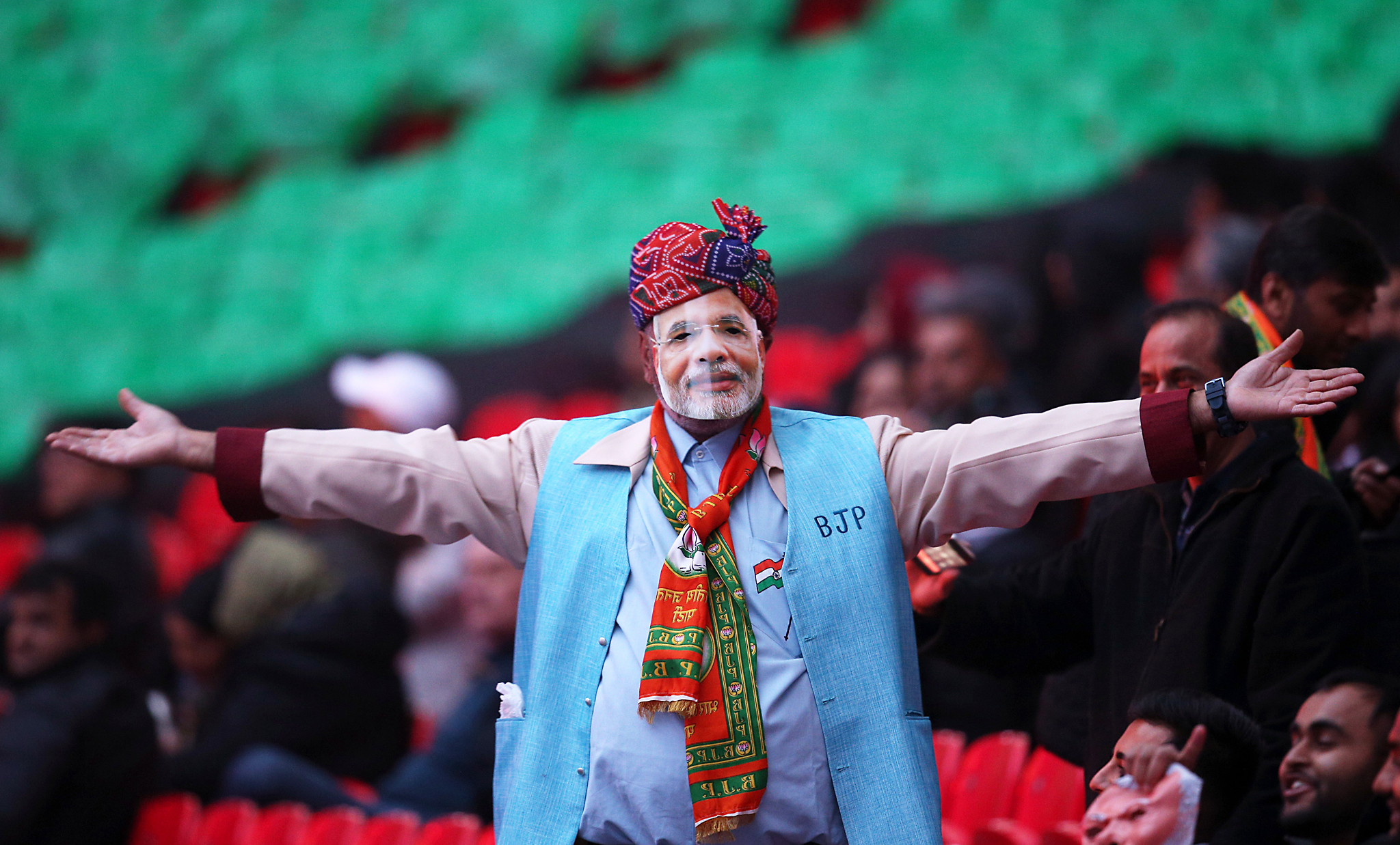 Wembley Welcomes Prime Minister Modi...LONDON, ENGLAND - NOVEMBER 13:  A man wearing a mask depicting Narendra Modi waves at Wembley Stadium prior to the Indian Prime Minister speaking, during the second day of an official three day visit on November 13, 2015 in London, England. Around 60,000 people including British Indians from 450 different community groups from around the country are expected to fill the stadium. A concert by an arts programme featuring 800 performers, including the Indian singing star Kanika Kapoor and the London Philharmonic Orchestra will entertain the crowd. Following Modi's address will be what is billed as one of the UKs largest ever firework displays.  (Photo by Dan Kitwood/Getty Images)