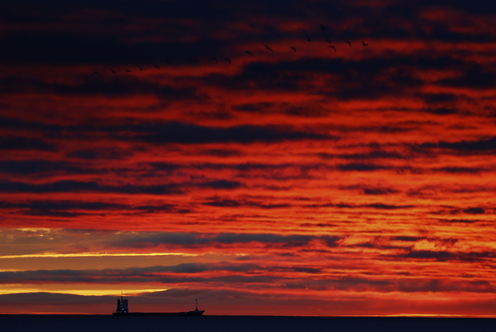 Autumn weather Nov 11th 2015...The sun rises over the North Sea off Whitley Bay, Tyne and Wear as a ship passes on the horizon. PRESS ASSOCIATION Photo. Picture date: Wednesday November 11, 2015. Photo credit should read: Owen Humphreys/PA Wire