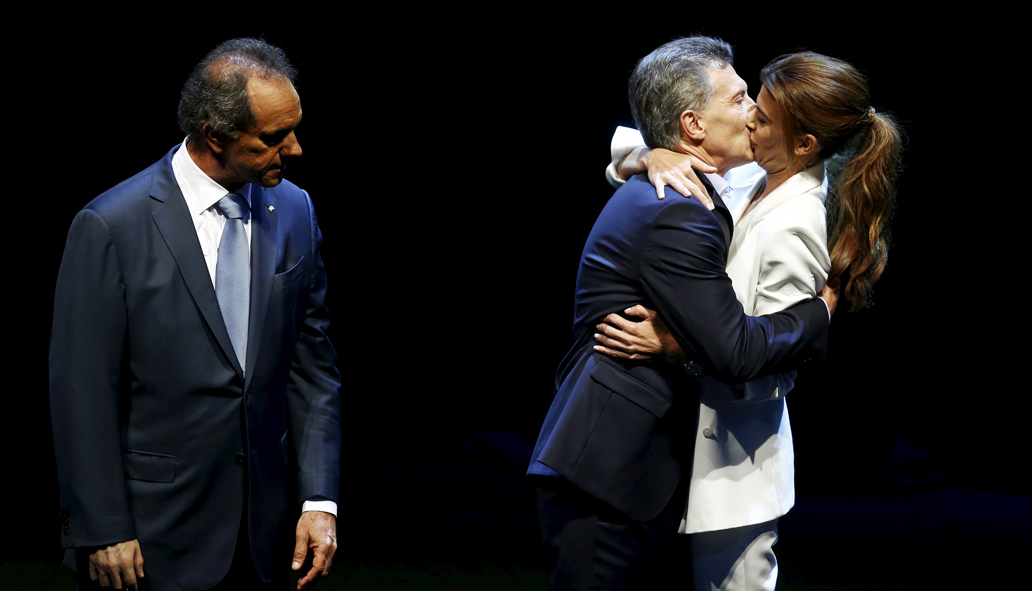 Macri, presidential candidate for the Cambiemos (Let's Change) alliance, kisses his wife Juliana Awada as Argentina's ruling party candidate Daniel Scioli watches at the end of the presidential debate ahead of November 22 run-off election in Buenos Aires