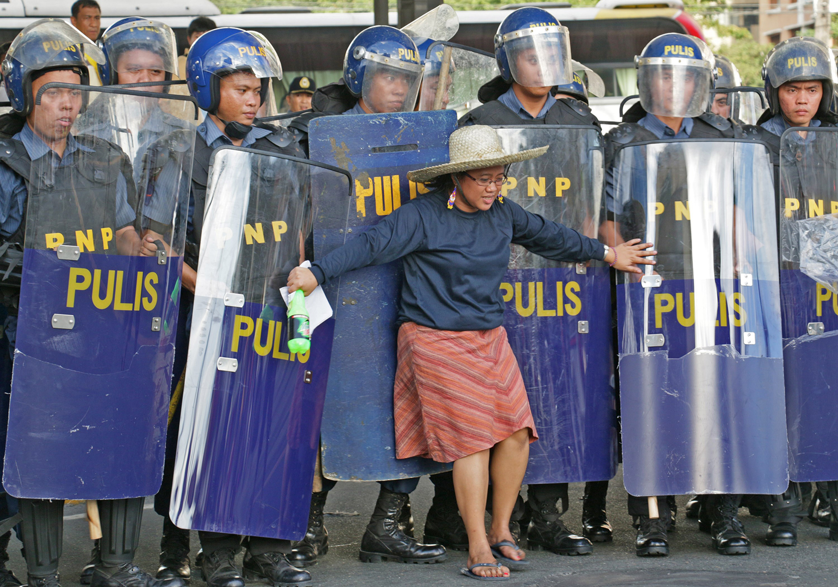 A woman stands in front of police as Filipino laborers clash with police