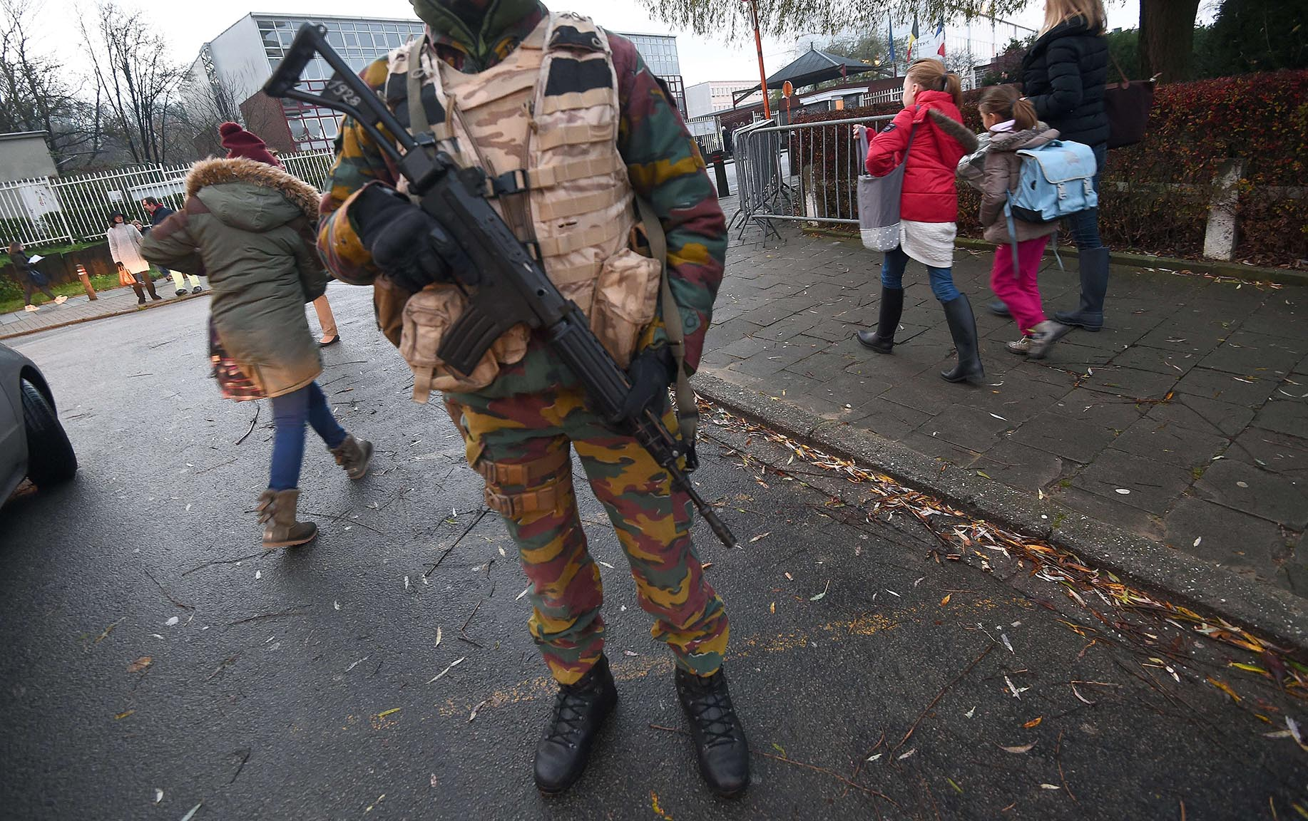 An armed soldier stand guards as pupils