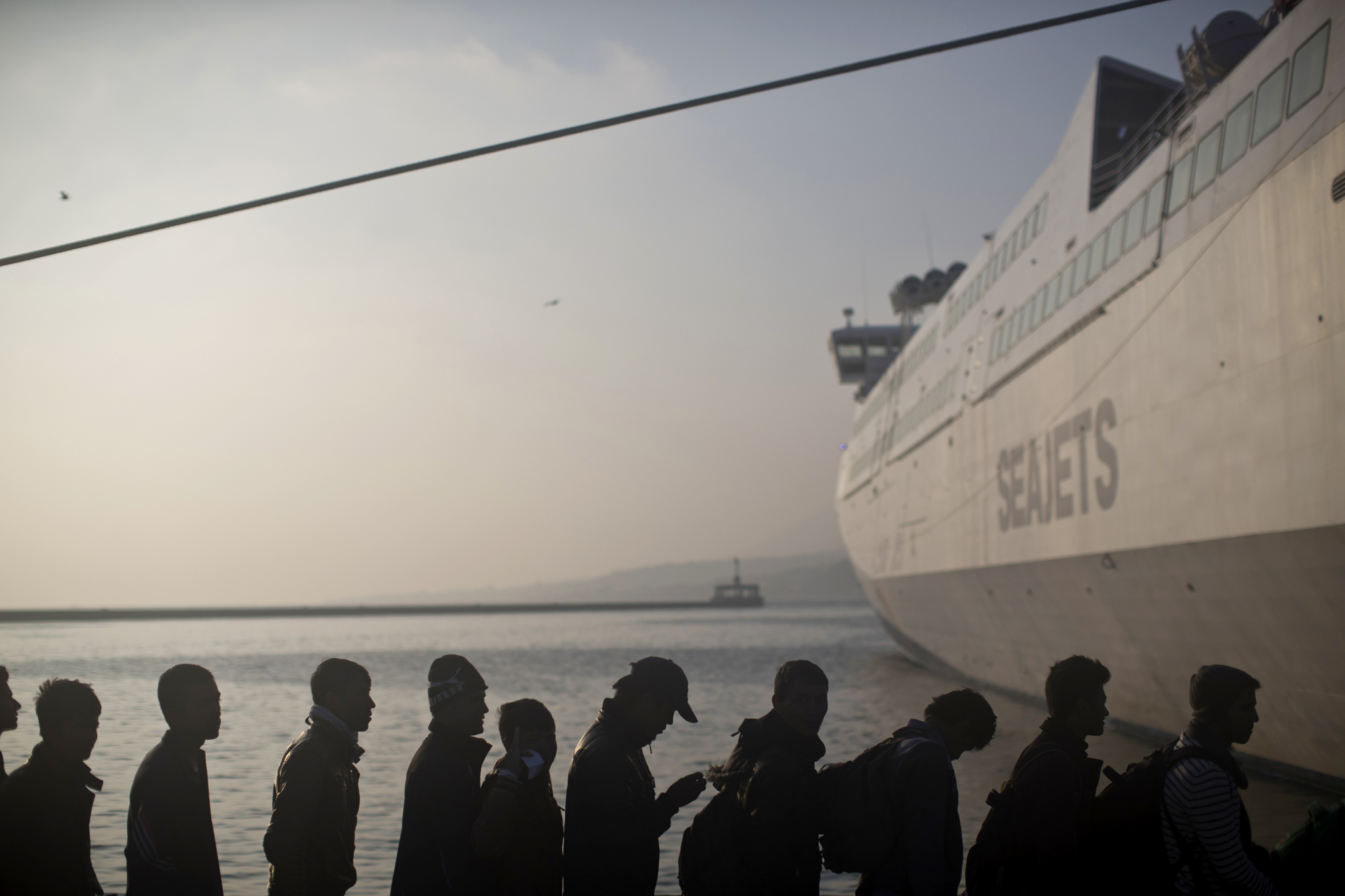 People queue in order to board a ferry at the port of Mytilene on the island of Lesbos, Greece