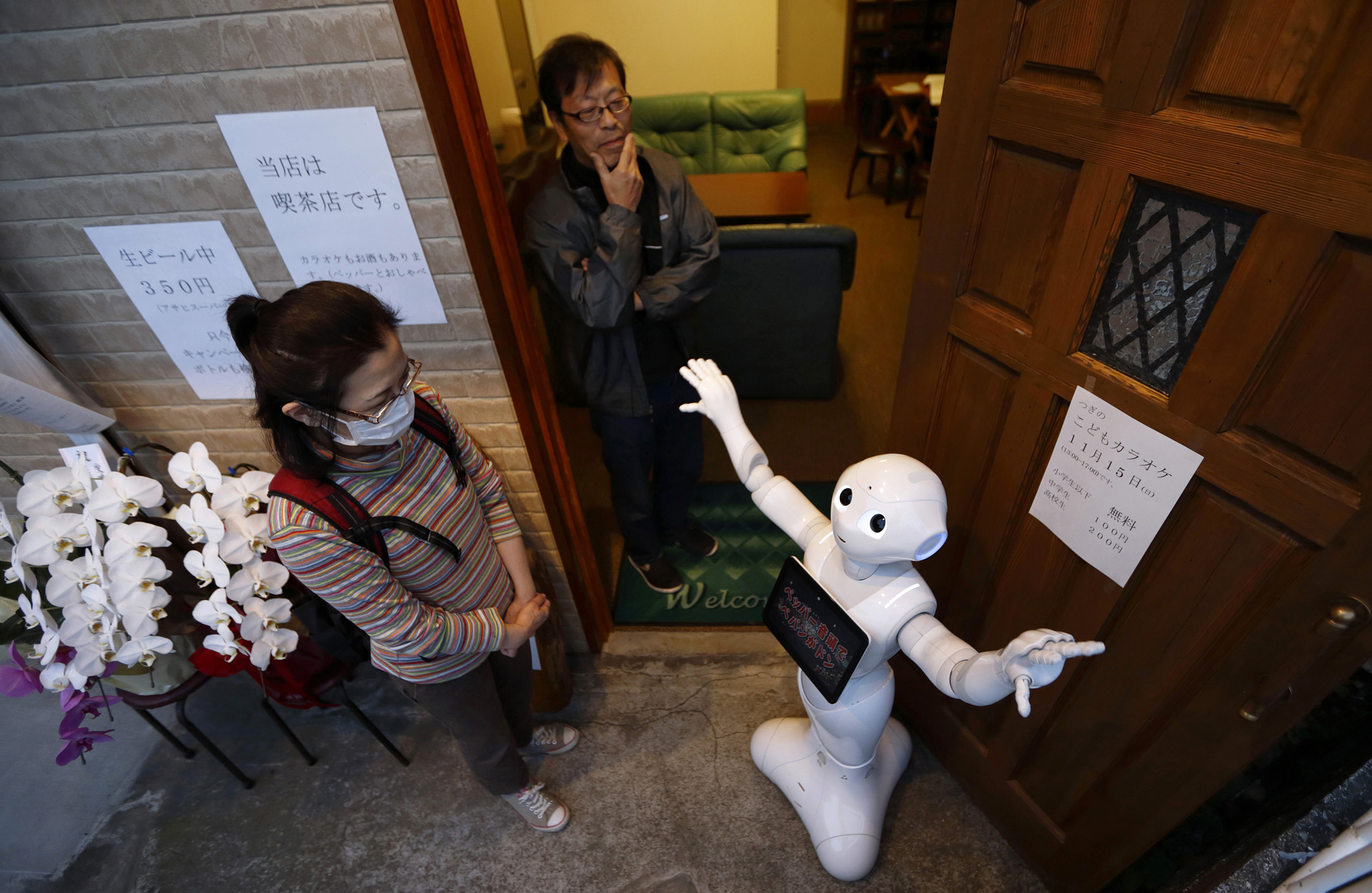 asahiko Yoshida, owner of a karaoke bar, center, looks on as a customer interacts with Pepper the humanoid robot