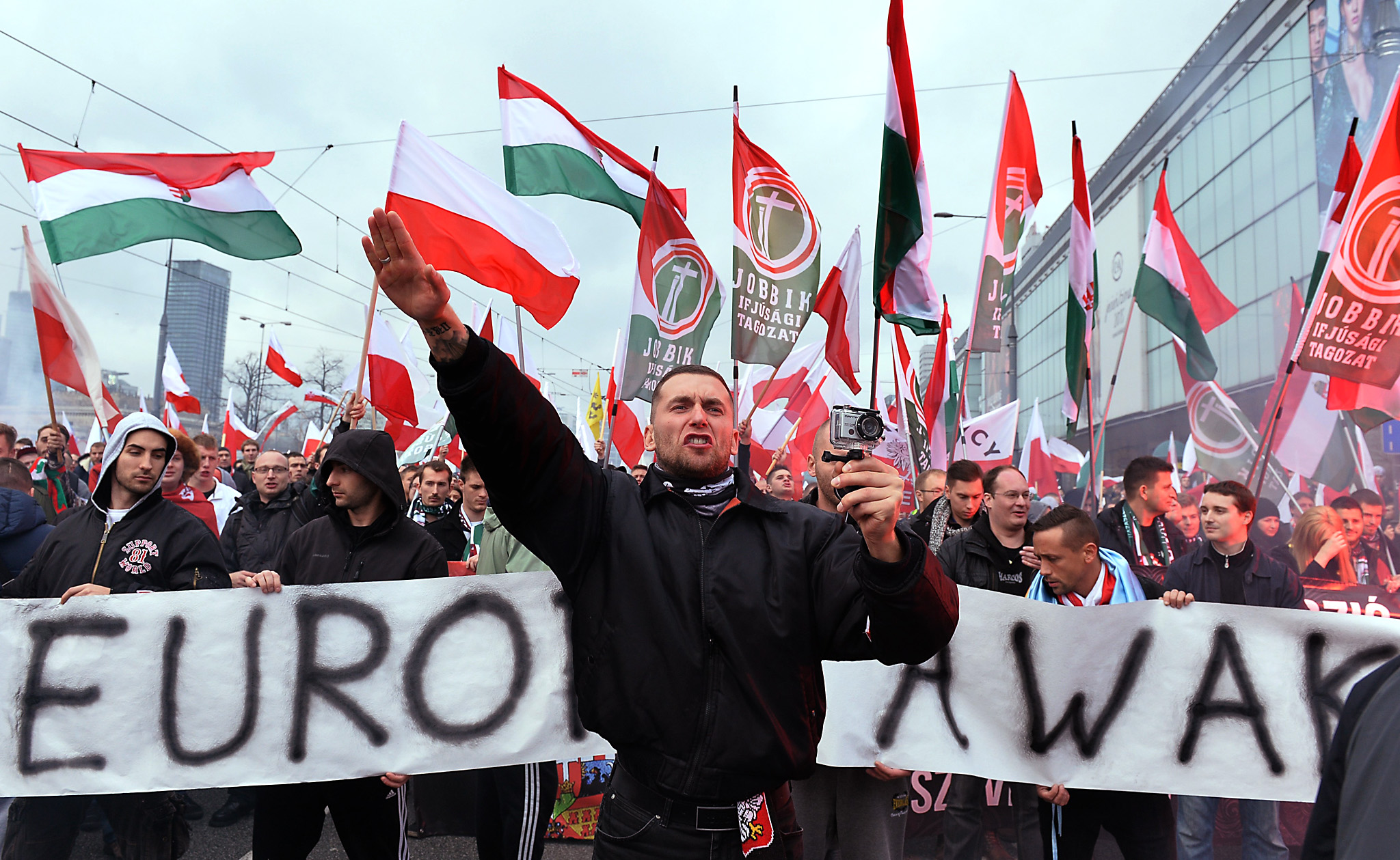 "POLAND-POLITICS-FARRIGHT-DEMO...A demonstrator shouts and performs a Nazi salute in front of banner reading ""Europe awake"" followed by a group of Hungarian Jobbik party representatives during an annual march commemorating Poland's National Independence Day in Warsaw on November 11, 2015. Poland's National Independence Day commemorates the anniversary of the Restoration of a Polish State in 1918. AFP PHOTO / JANEK SKARZYNSKI        (Photo credit should read JANEK SKARZYNSKI/AFP/Getty Images)"