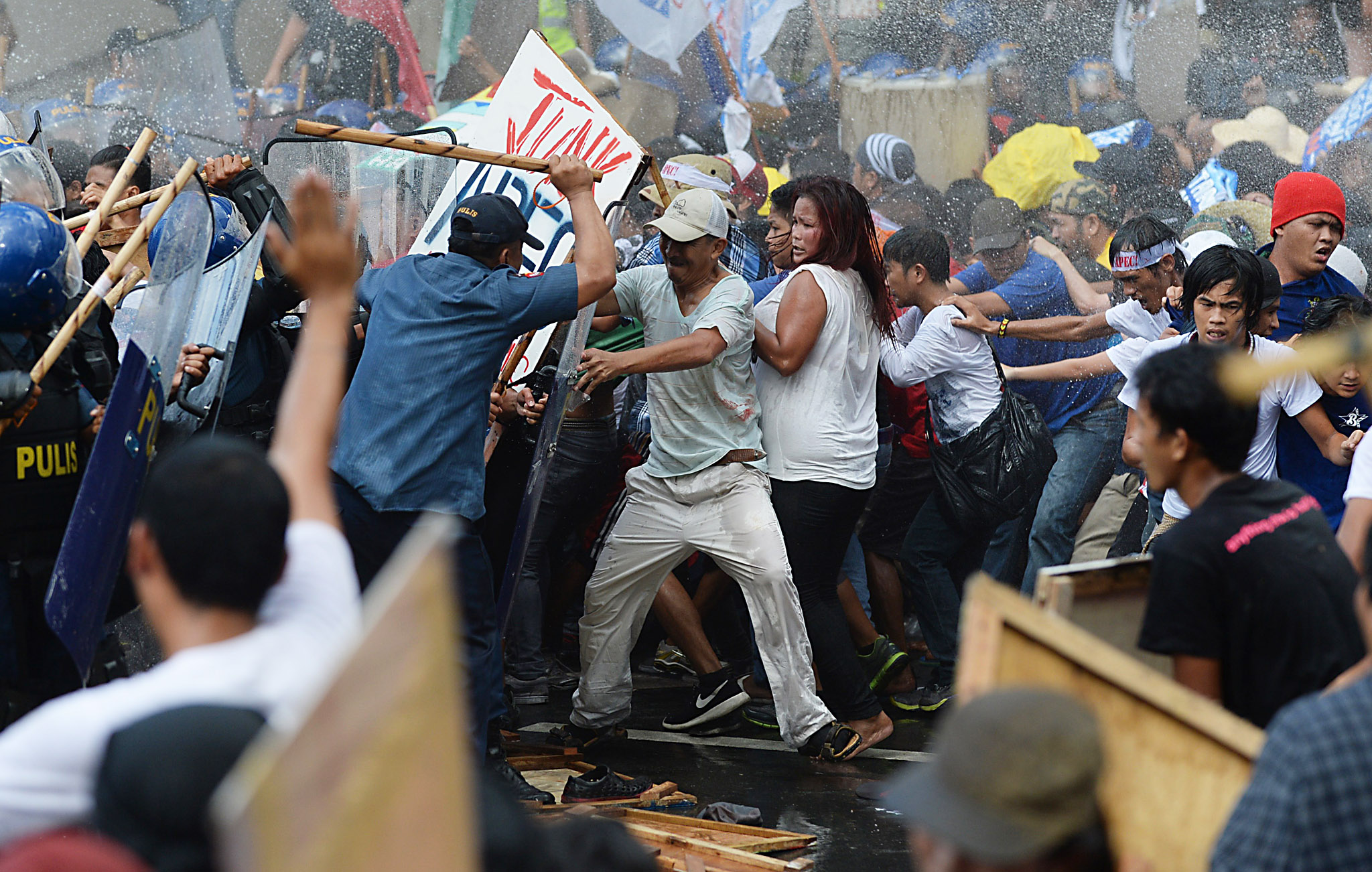 TOPSHOTS Philippine police (L) fire water cannon as they clash with protesters (R) parading down a street trying to voice their opposition to the Asia-Pacific Economic Cooperation (APEC) Summit currently taking place in Manila on November 19, 2015. Asia-Pacific leaders are wrapping up two-days of talks in Manila that have been overshadowed by an arm-wrestle for regional influence between the United States and China. AFP PHOTO / Punit PARANJPEPUNIT PARANJPE/AFP/Getty Images