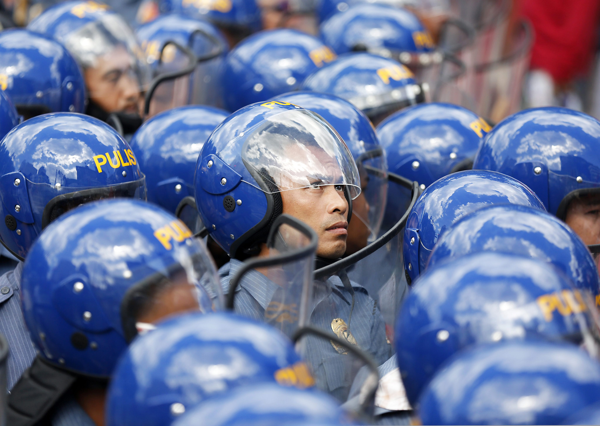 Protest against the APEC 2015 in Manila...epa05028990 A Filipino boy runs in front of a line of riot police officers during a protest rally at a street in Manila, Philippines, 17 November 2015. Philippine security forces were on high alert in the capital as leaders from Asia and the Pacific region began to arrive for the Asia-Pacific Economic Cooperation (APEC) summit just days after the deadly terrorist attacks in France.  EPA/FRANCIS R. MALASIG