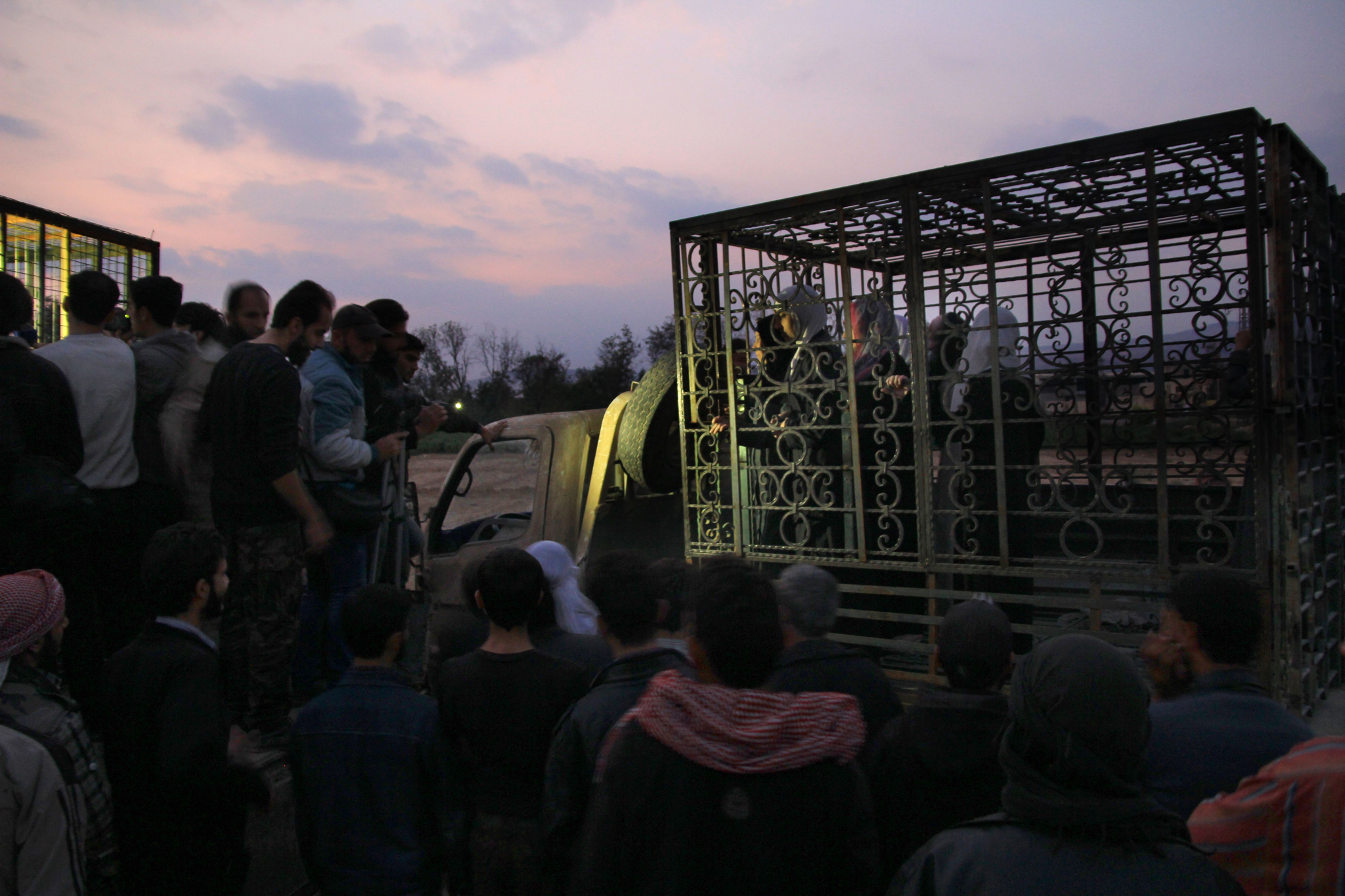 """TOPSHOTS Syrians are seen inside a cage ...TOPSHOTS Syrians are seen inside a cage in Douma, the largest opposition stronghold on the outskirts of Damascus, on October 31, 2015, as it has been reported that a major Syrian rebel group is using dozens of captives in metal cages as """"human shields"""". Jaish al-Islam, regarded as the most powerful rebel group near the capital, has put regime soldiers and Alawite civilians it was holding in metal cages, the Syrian Observatory for Human Rights told AFP. AFP PHOTO / AHMAD AL-FAROQAHMAD AL-FAROQ/AFP/Getty Images"""