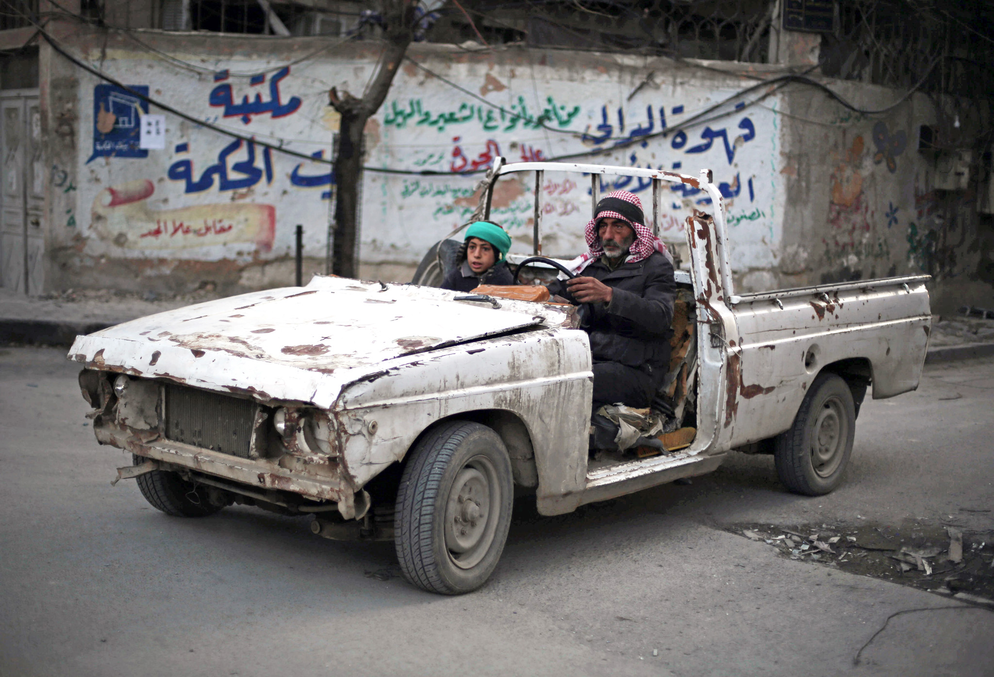 A Syrian man and his son drive in vehicle battered by years on conflict in the rebel-held area of Douma, east of the capital Damascus, on November 10, 2015.