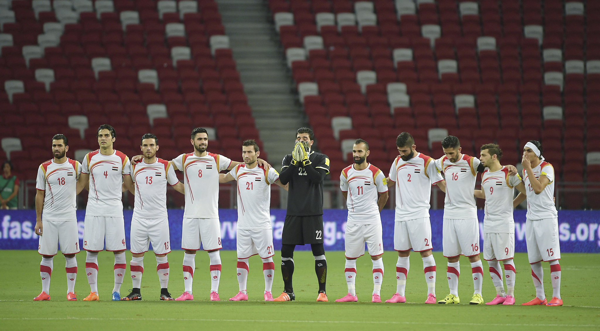 The national soccer team of Syria observes a moment of silence for last week's attacks in Paris ahead of their second round soccer match of regional qualifiers against Singapore for the 2018 World Cup, Tuesday, Nov. 17, 2015 in Singapore. WLD(AP Photo/Joseph Nair)